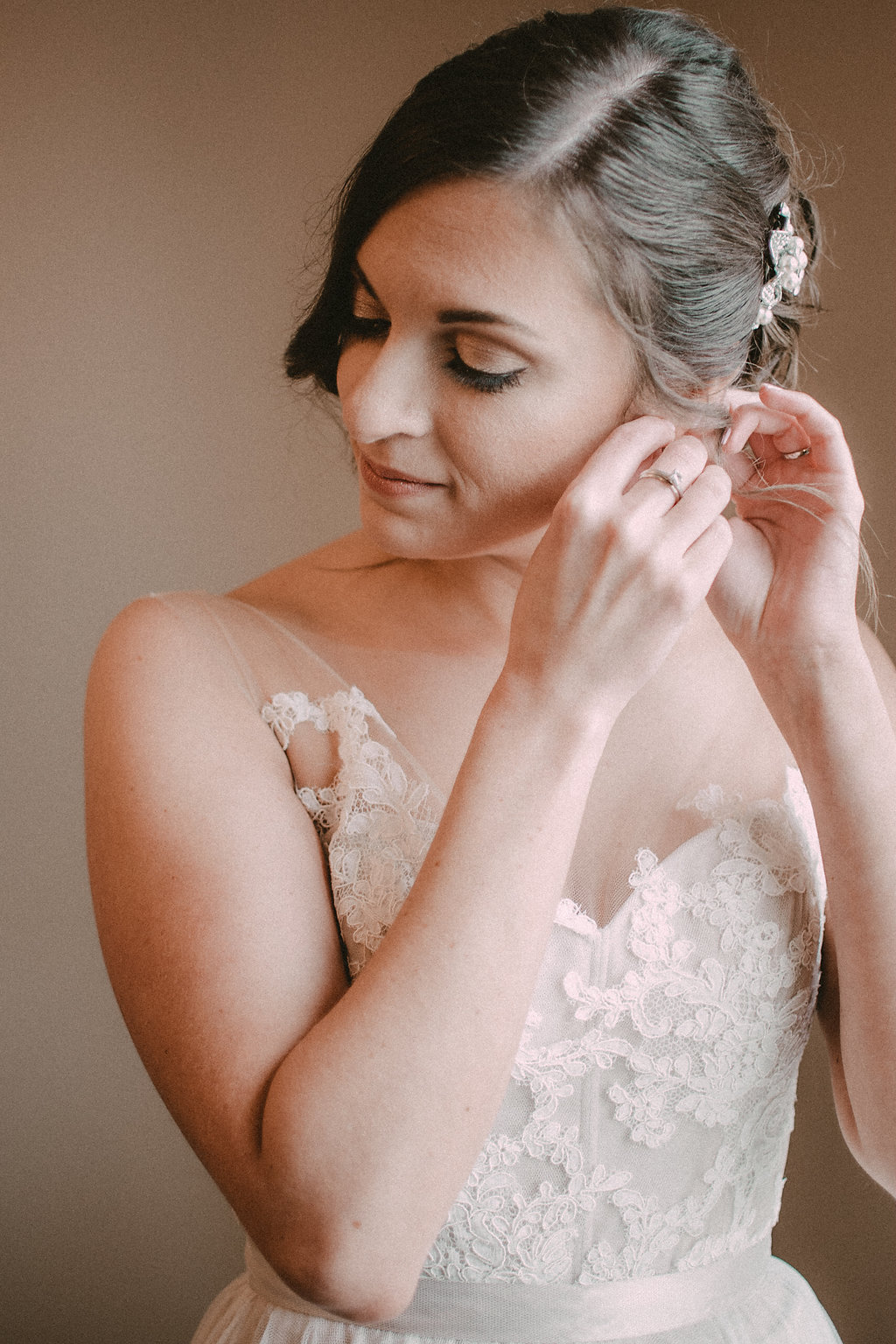 Bride putting on earrings in wedding dress