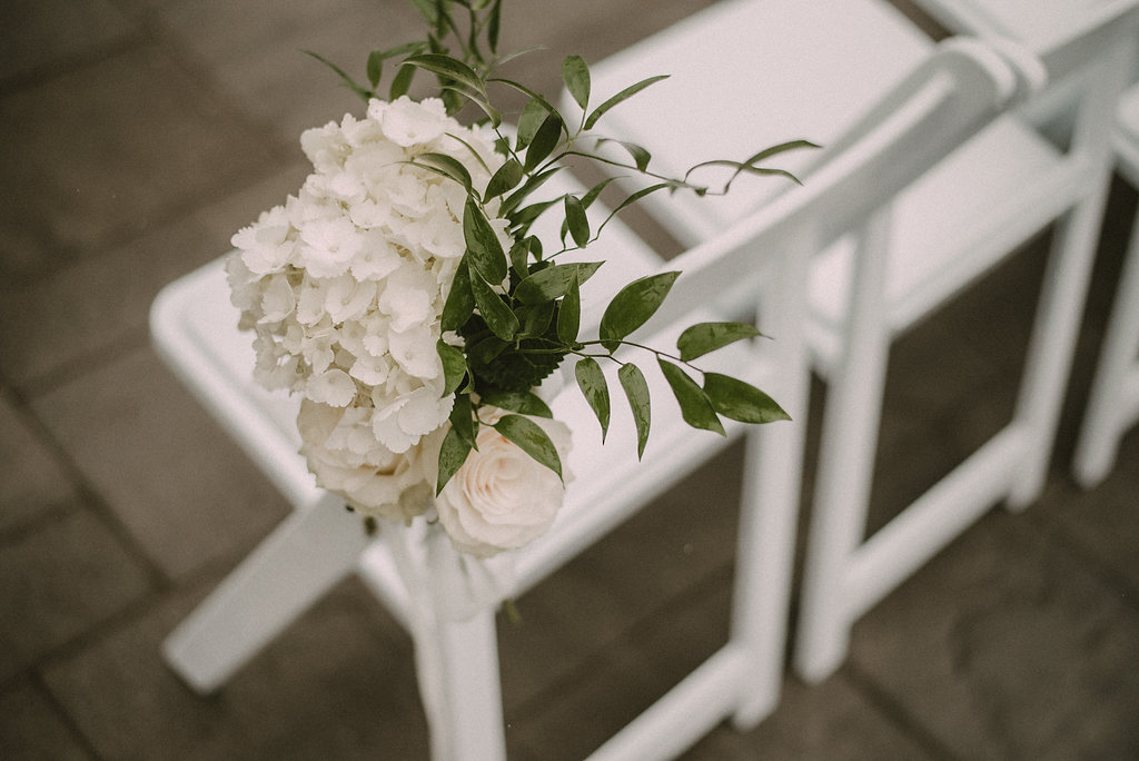 Flowers on wedding chair in ceremony space