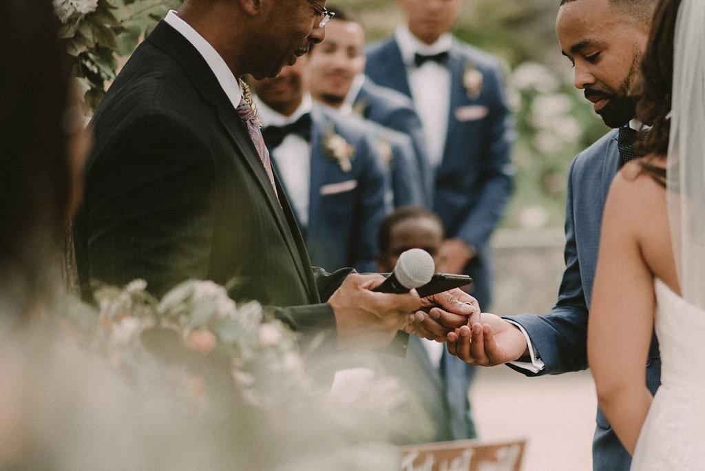 wedding officiant handing groom rings photo