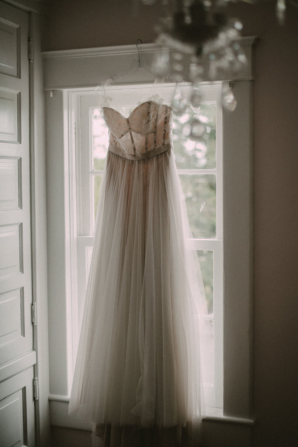 Wedding and pink bridesmaids dresses hanging in a row