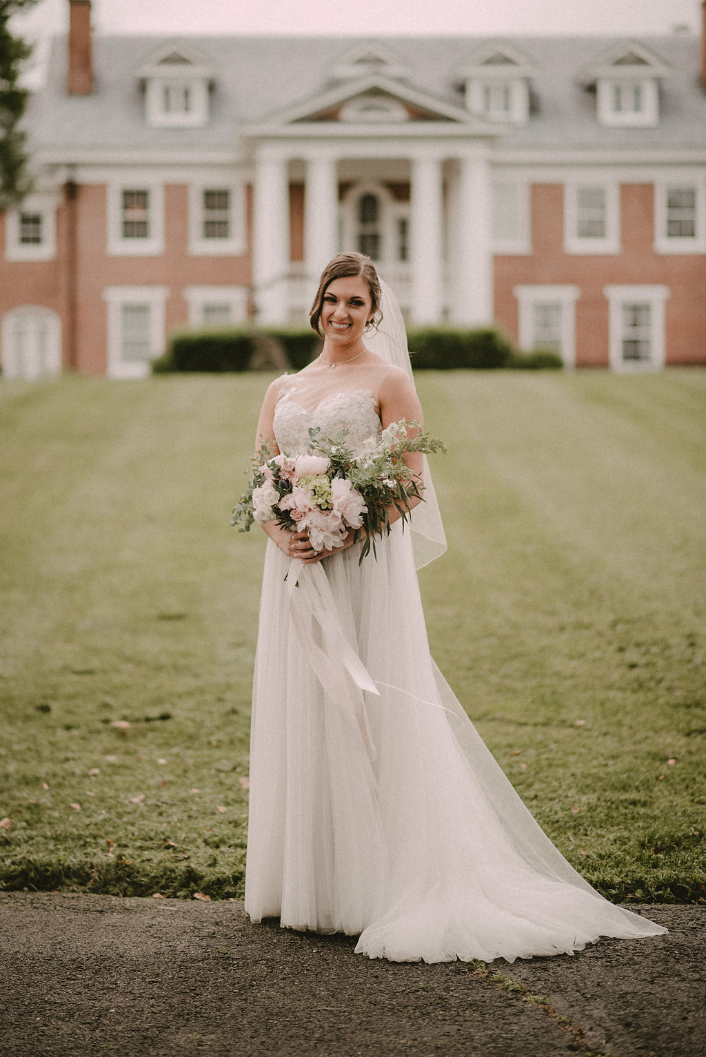 Bride standing in front of southern manor