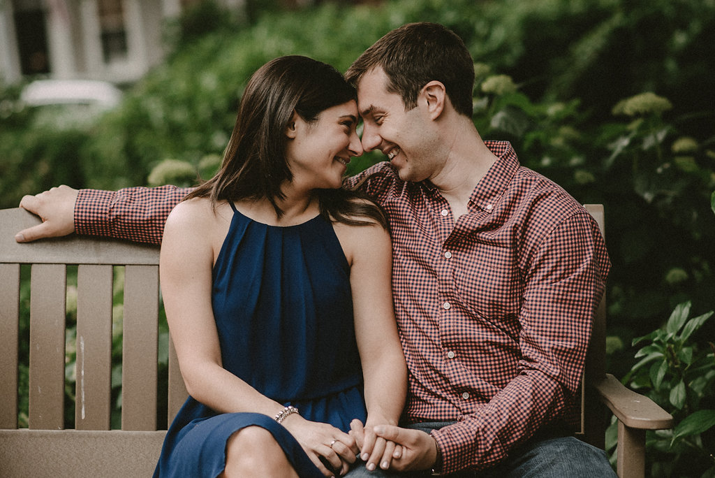 Couple sitting on park bench engagement photo