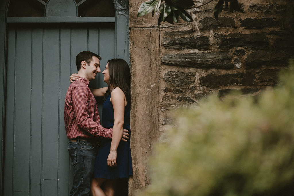 Couple kissing by brick wall and blue door