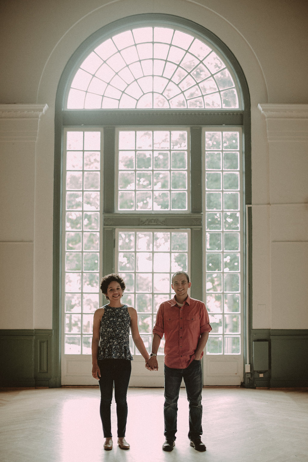 Couple holding hands in front of window