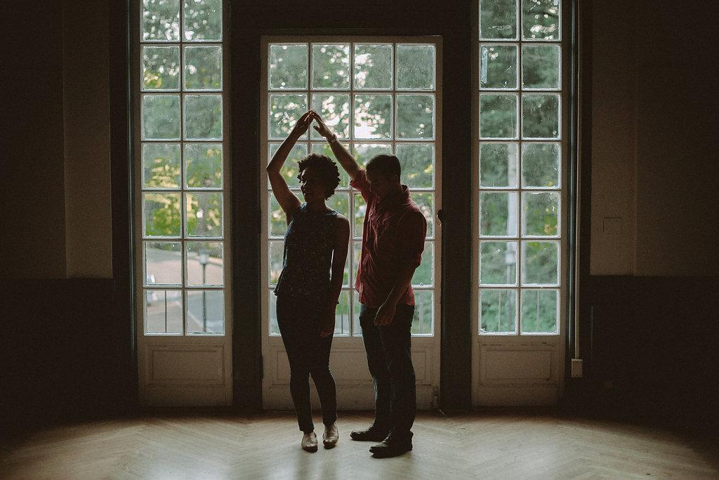 Couple dancing in front of window