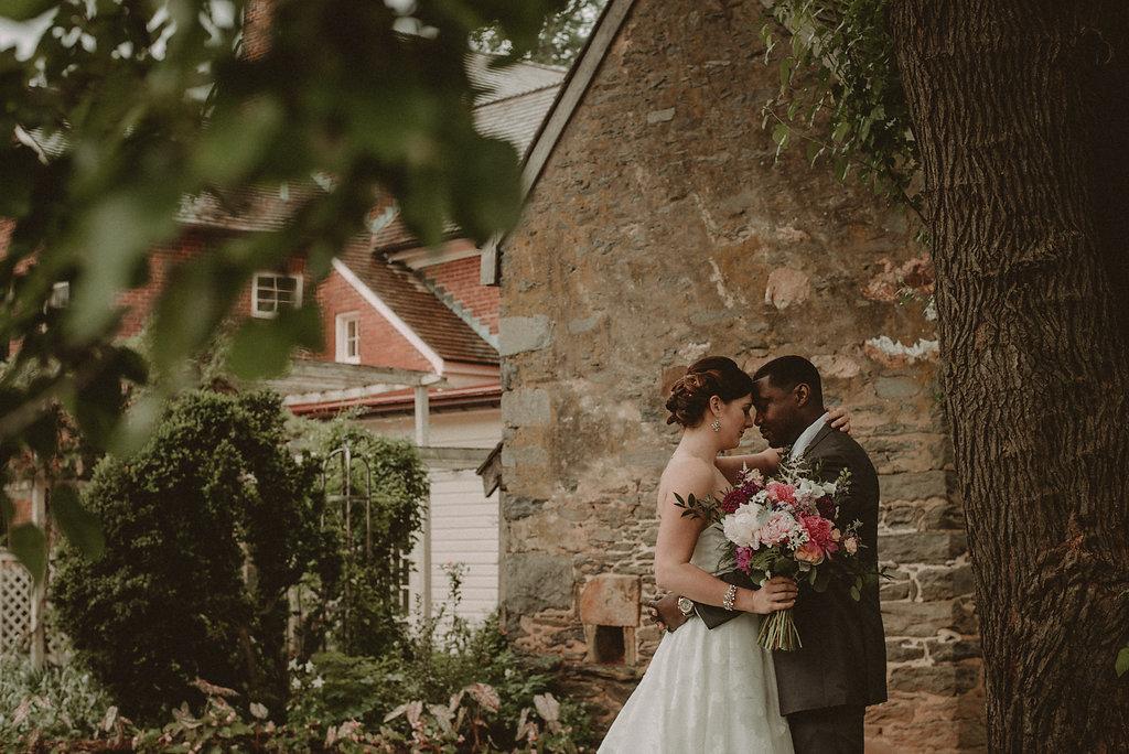 Bride and groom hug under tree