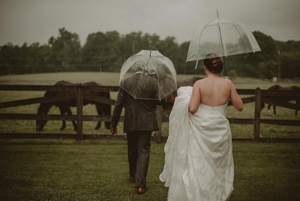 Bride and groom walking in rain