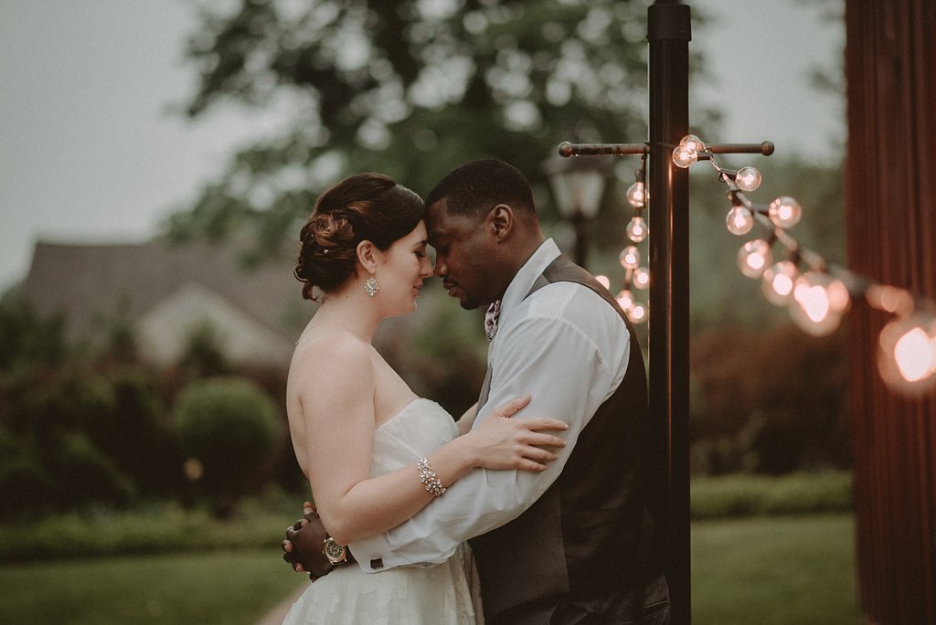 Bride and groom posing by lights