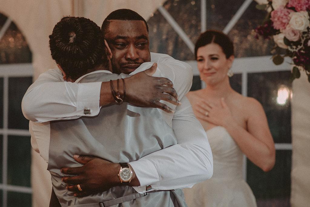 Groom and groomsmen hugging at reception