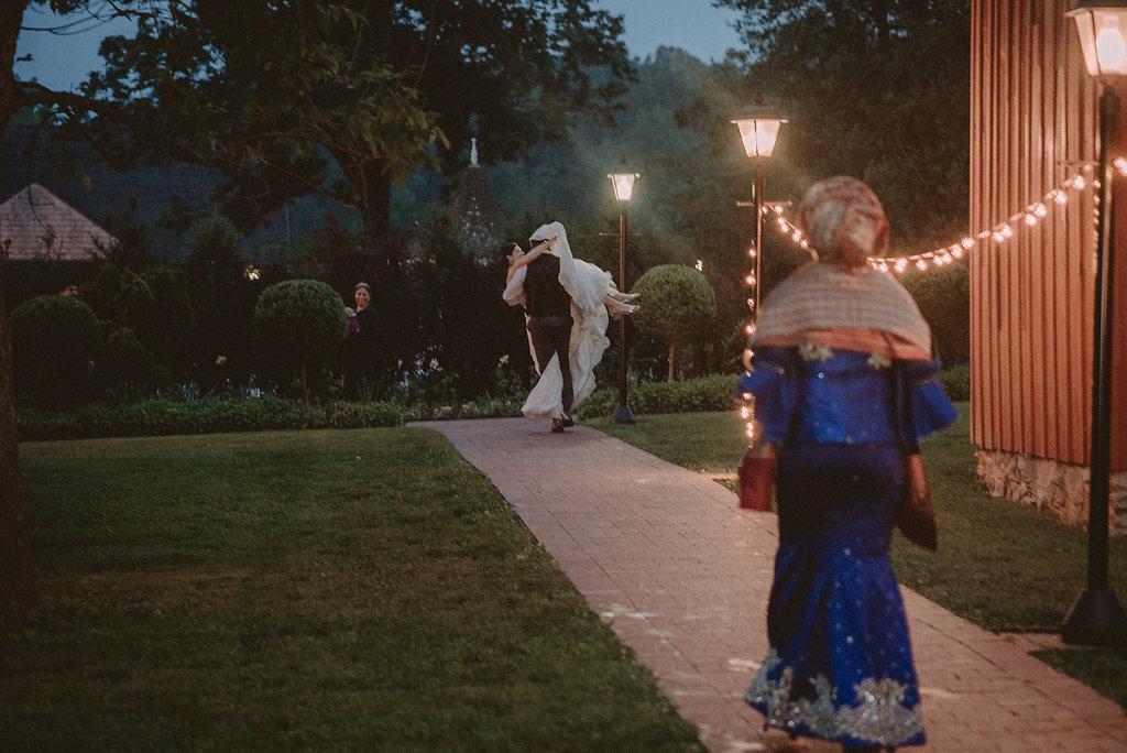 Groom carrying bride at wedding