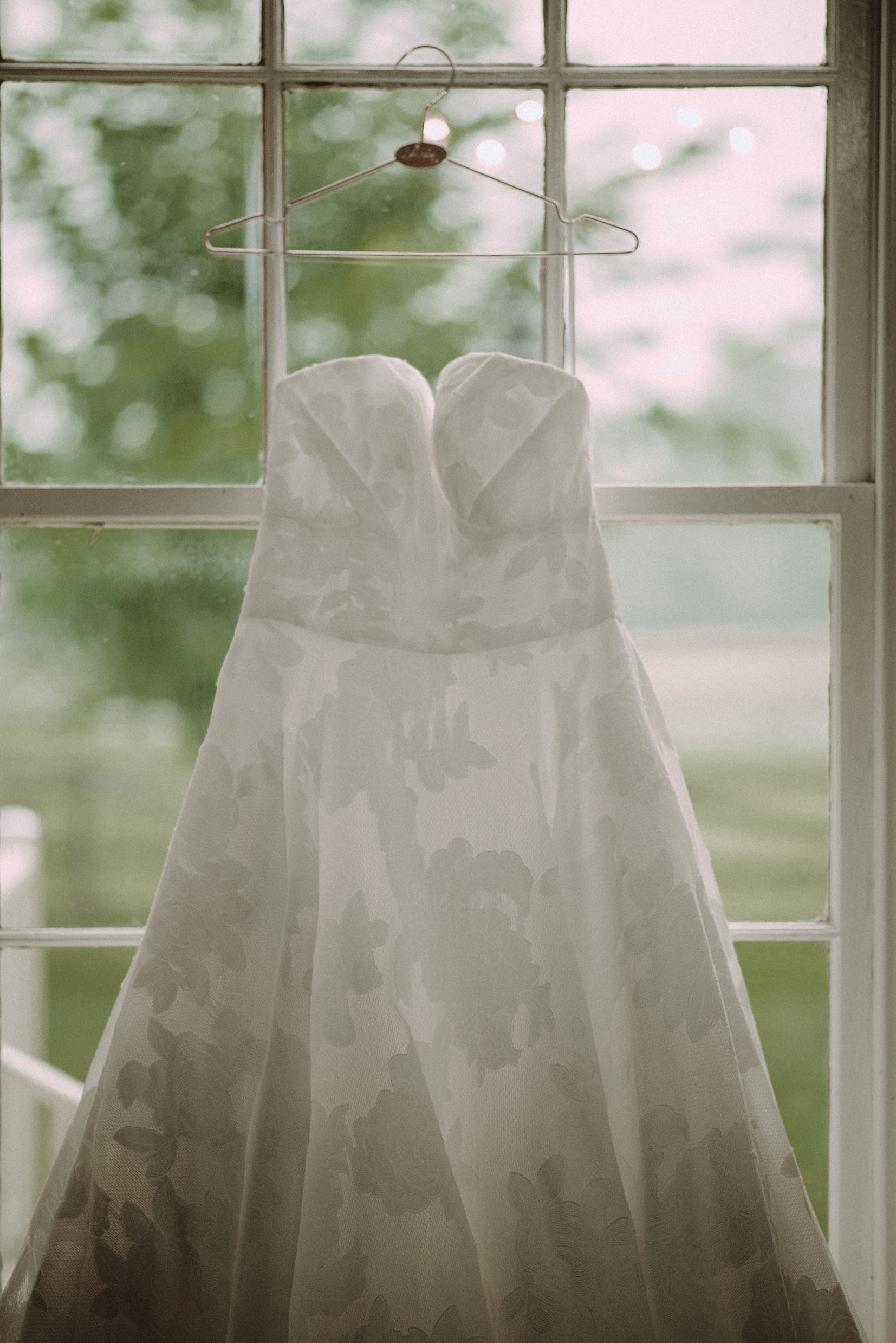 Wedding dress hanging in window