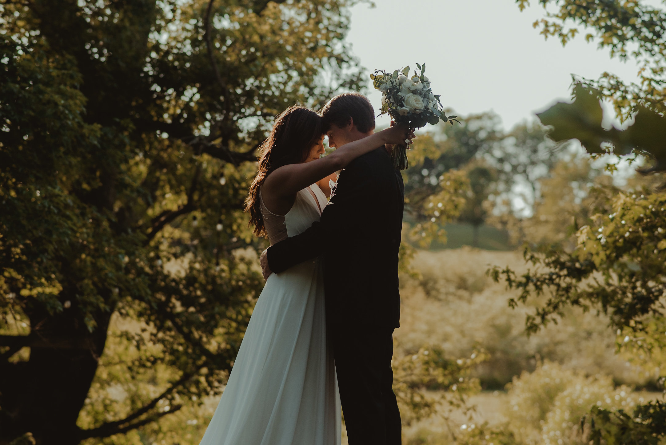 Bride and groom embracing in sunlight