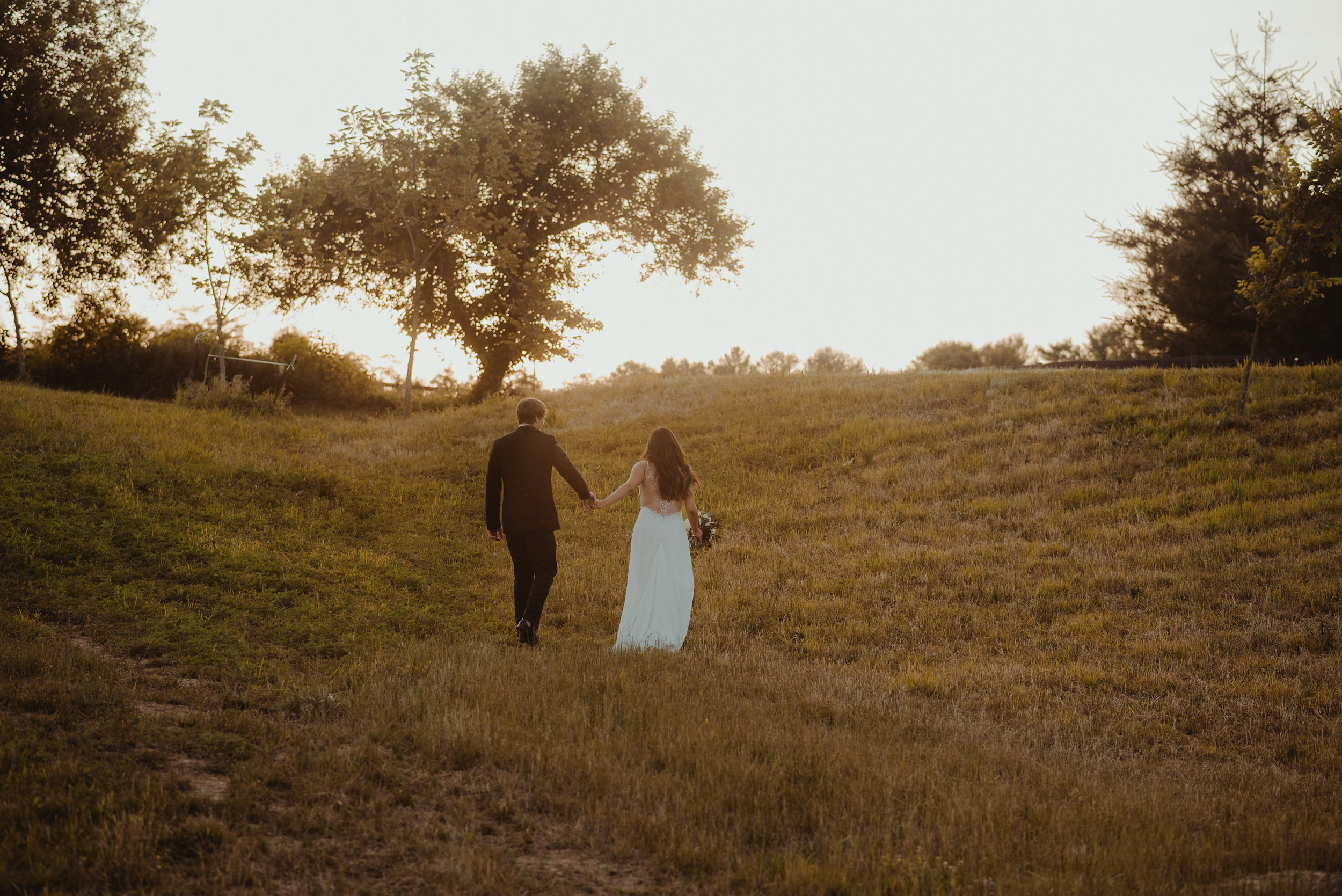 Bride and groom walking into sunset