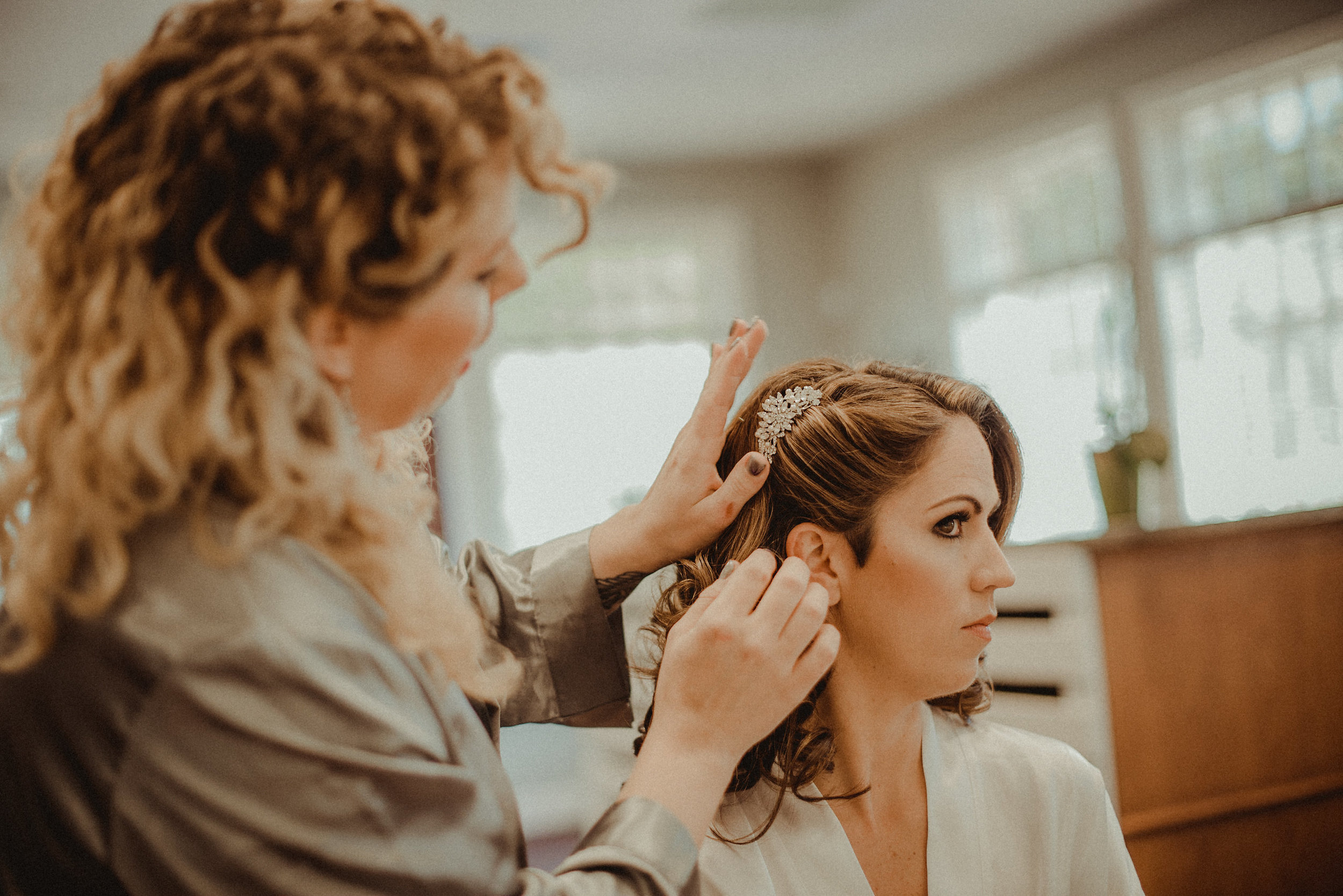 Bride having hair done for wedding