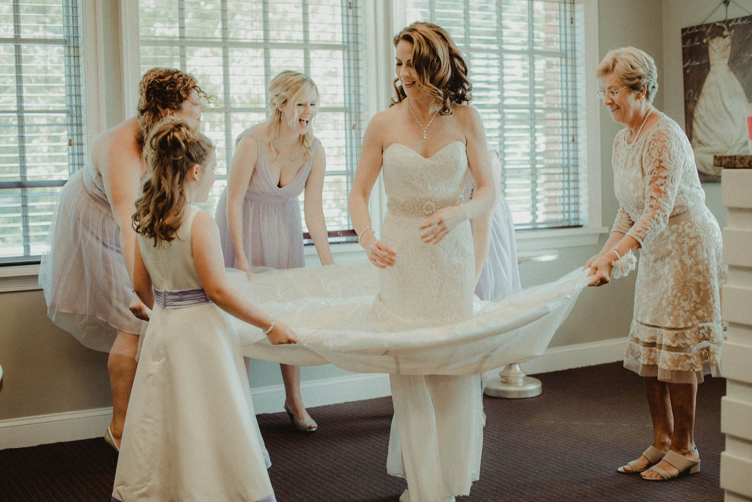 Bridal party helping bride dress