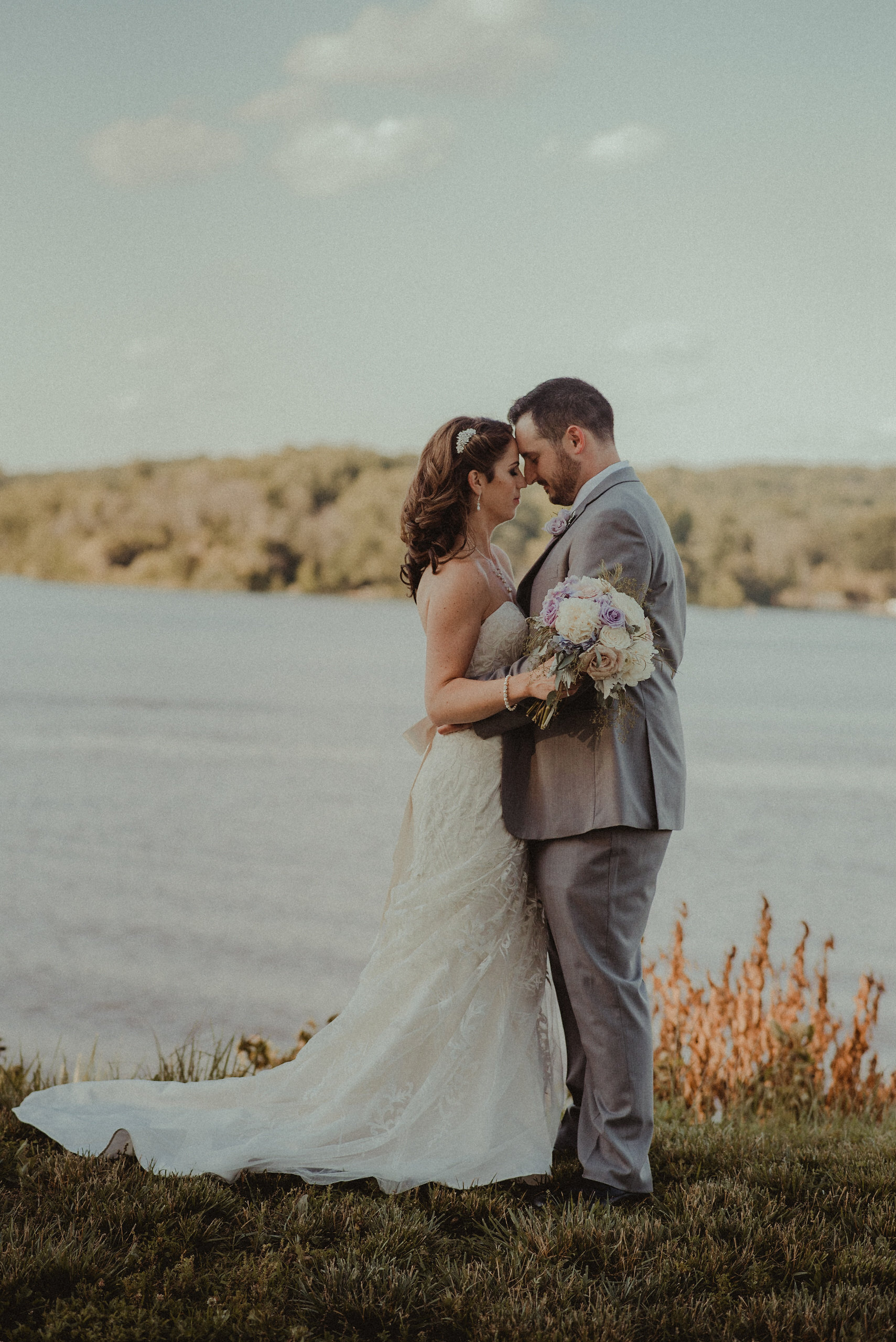 Bride and groom kissing in front of lake