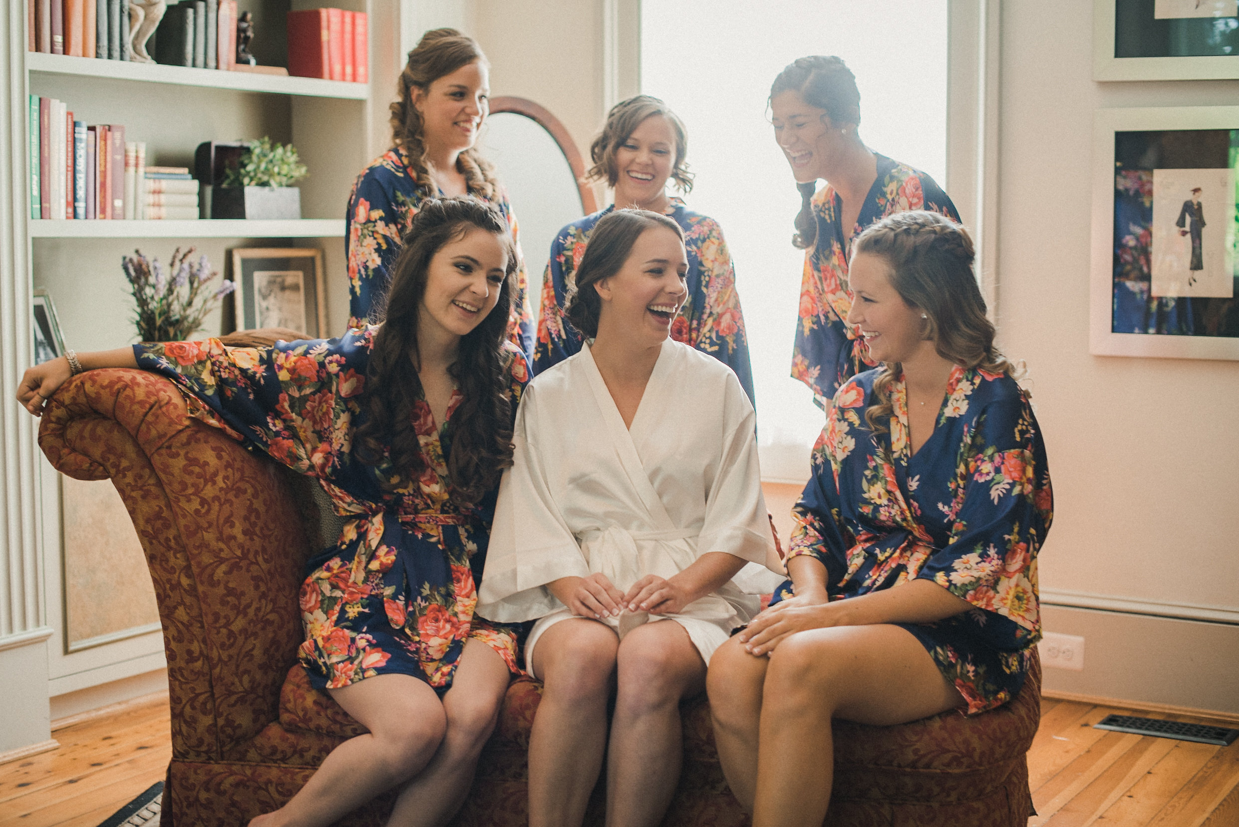 Bride sitting on couch with bridesmaids