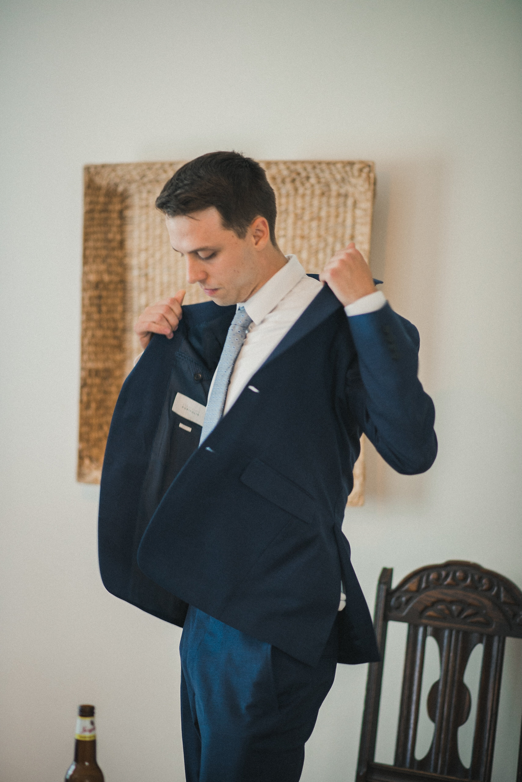 Groom putting on jacket