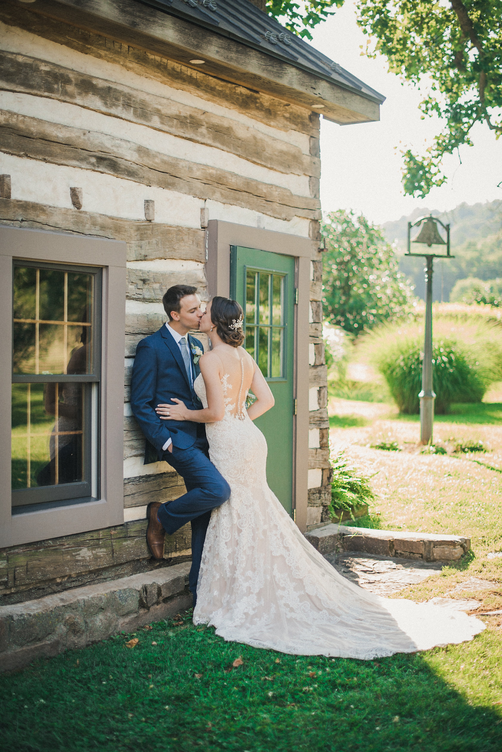 Bride and groom kissing at cabin