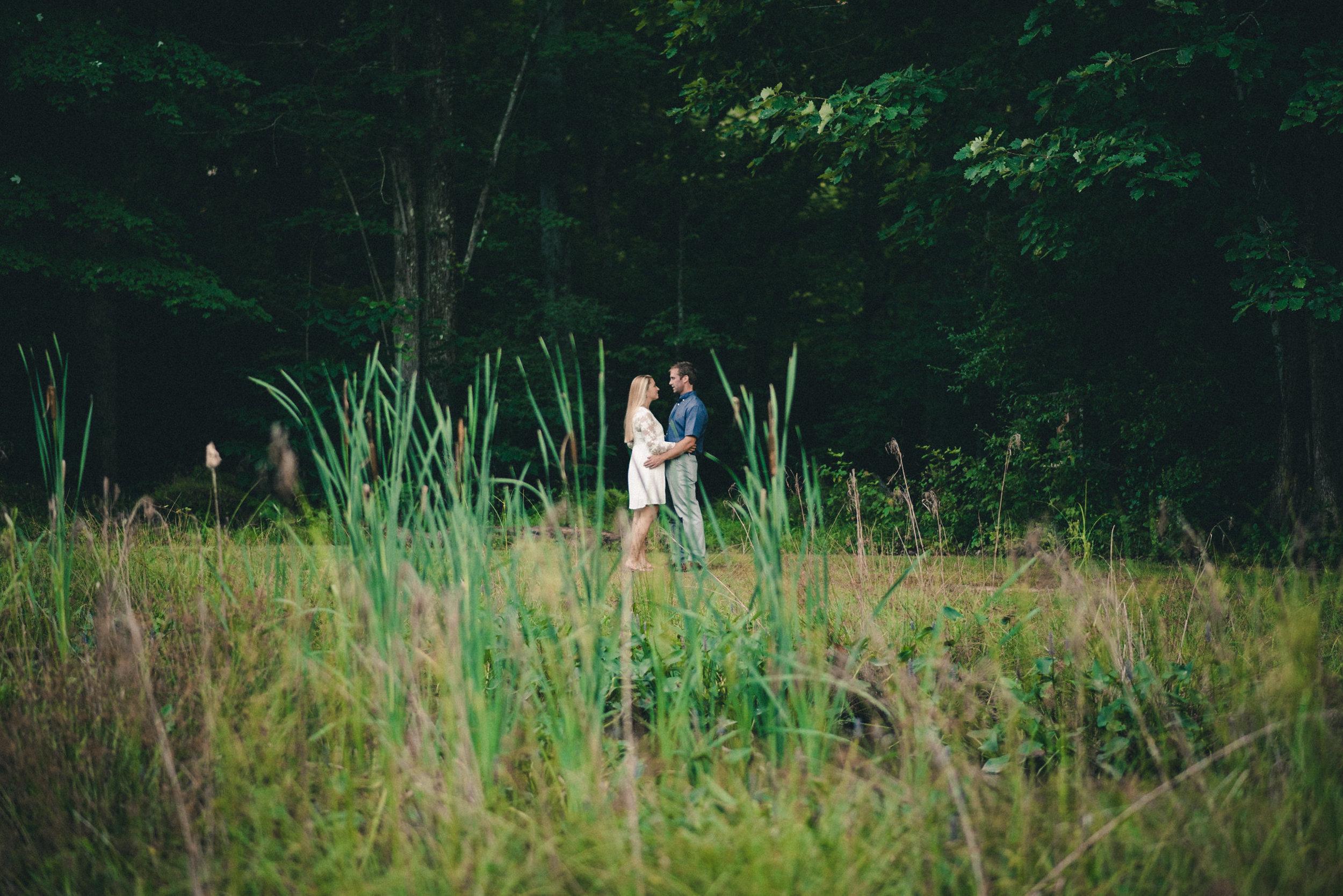 Couple from far away through tall grass