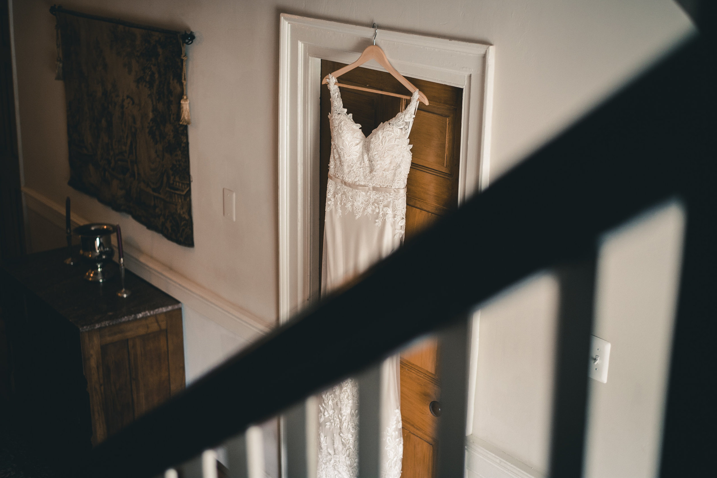 Wedding dress hanging on a door down the stairs