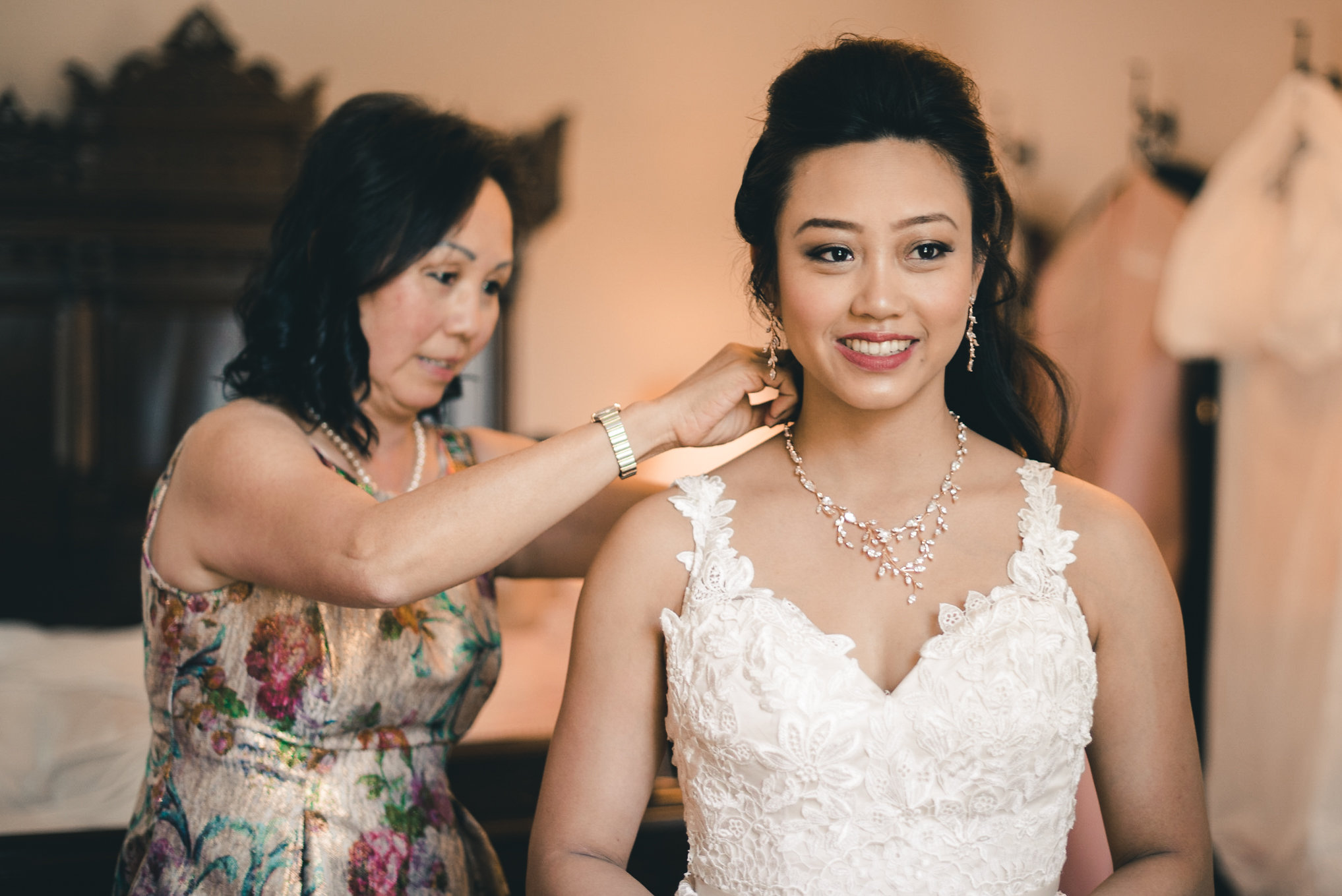 Mother putting necklace on bride