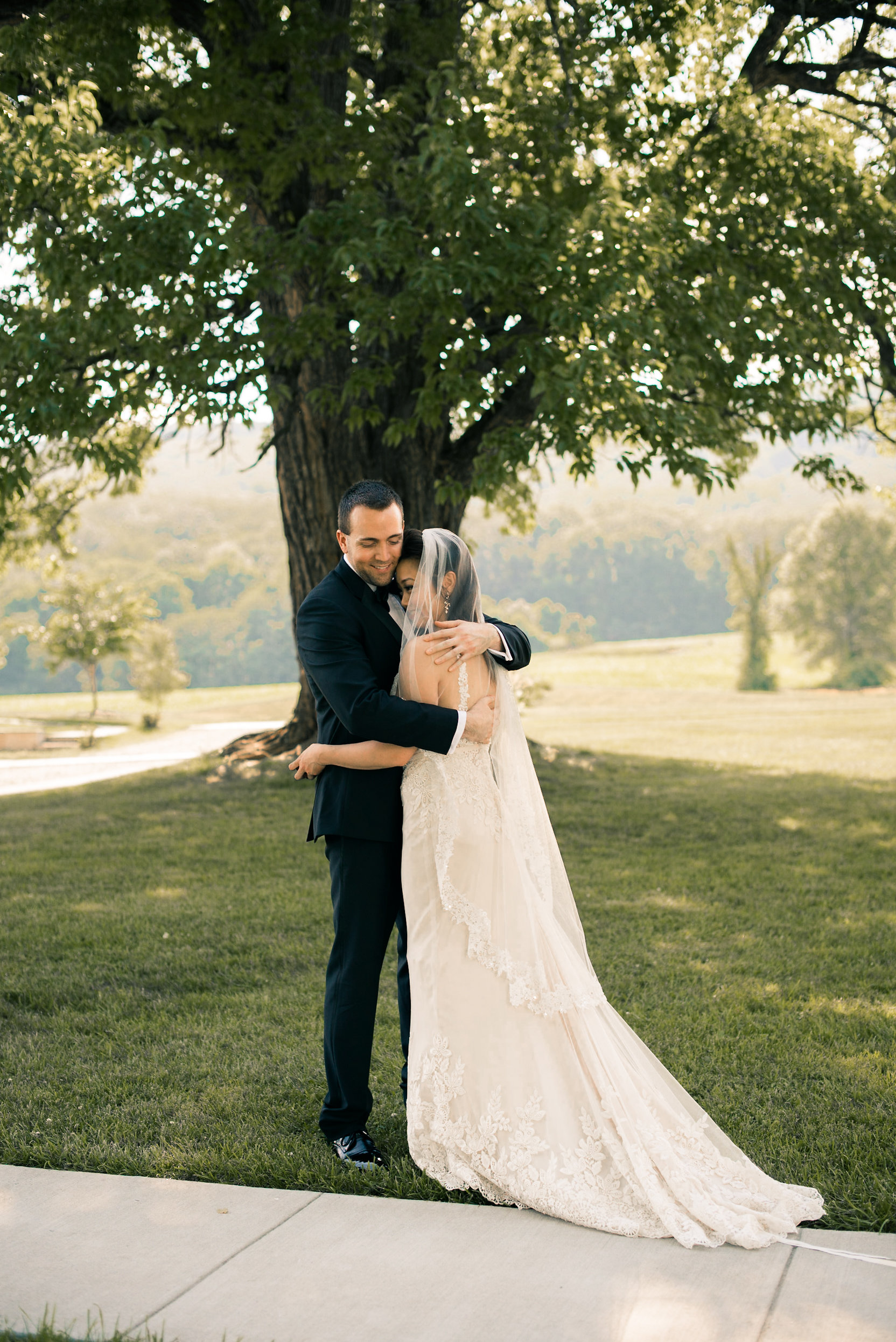 Bride and groom embrace under tree