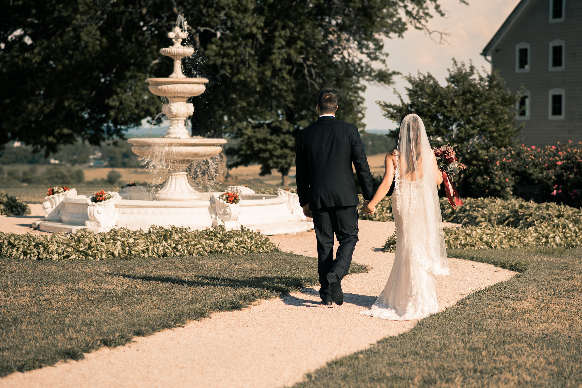 Bride and groom walking by fountain