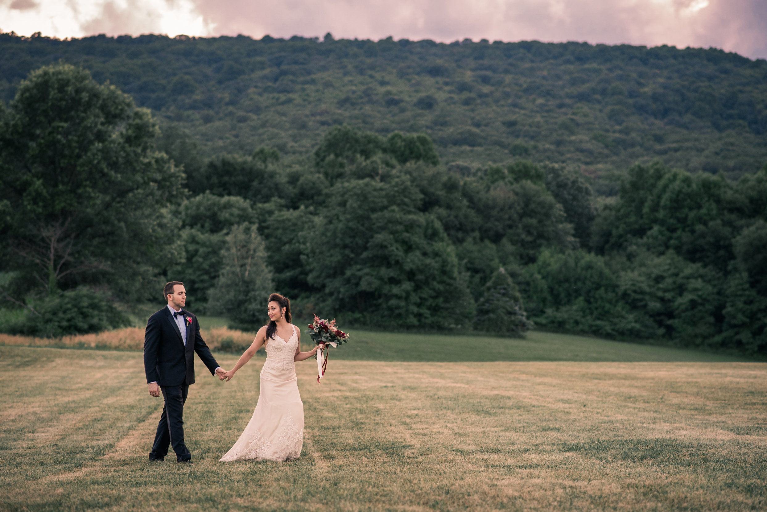 Bride and groom walking through field by mountain