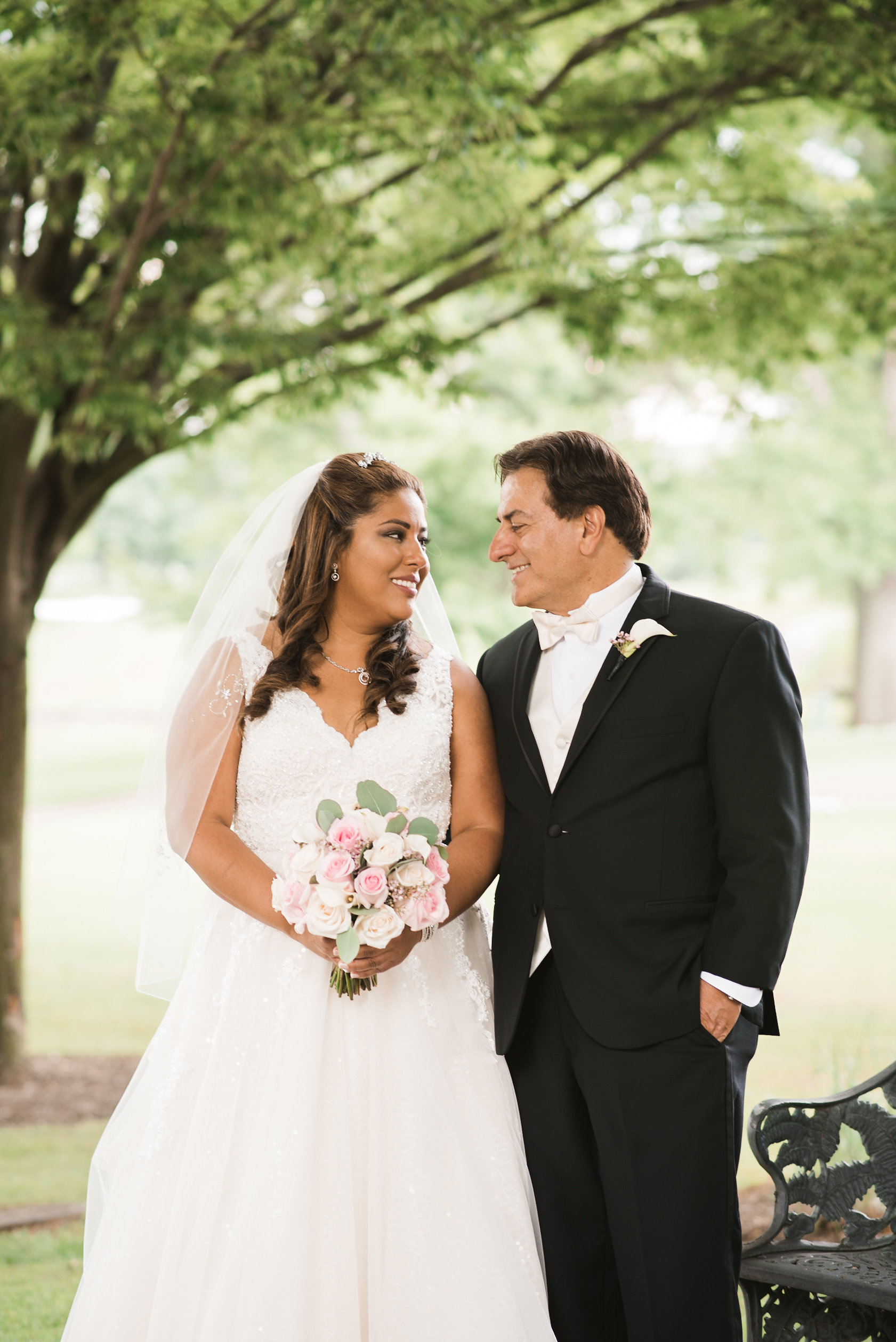 Bride and groom under tree by bench