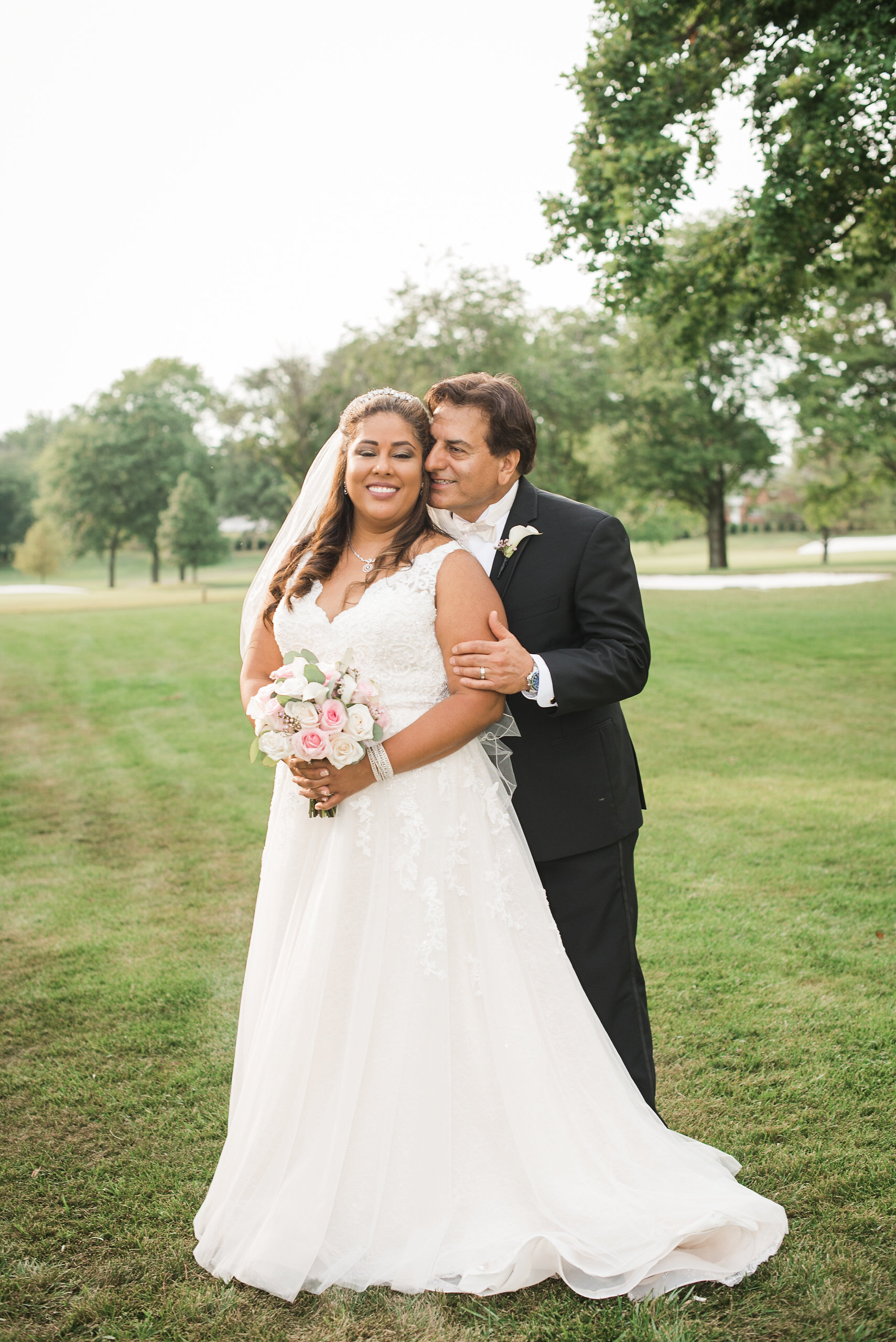 Bride and groom posing on grass