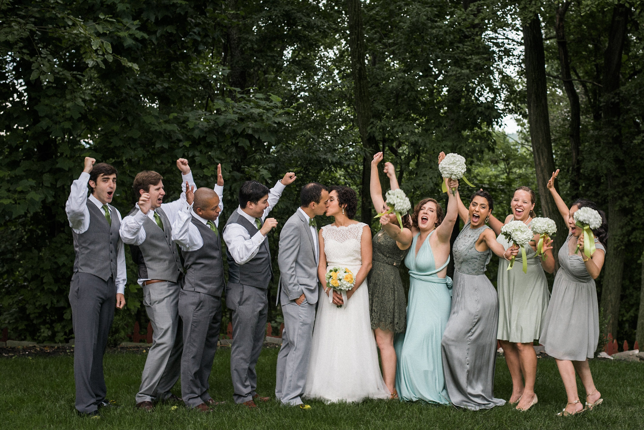 Groom and bride kissing in front of bridal party