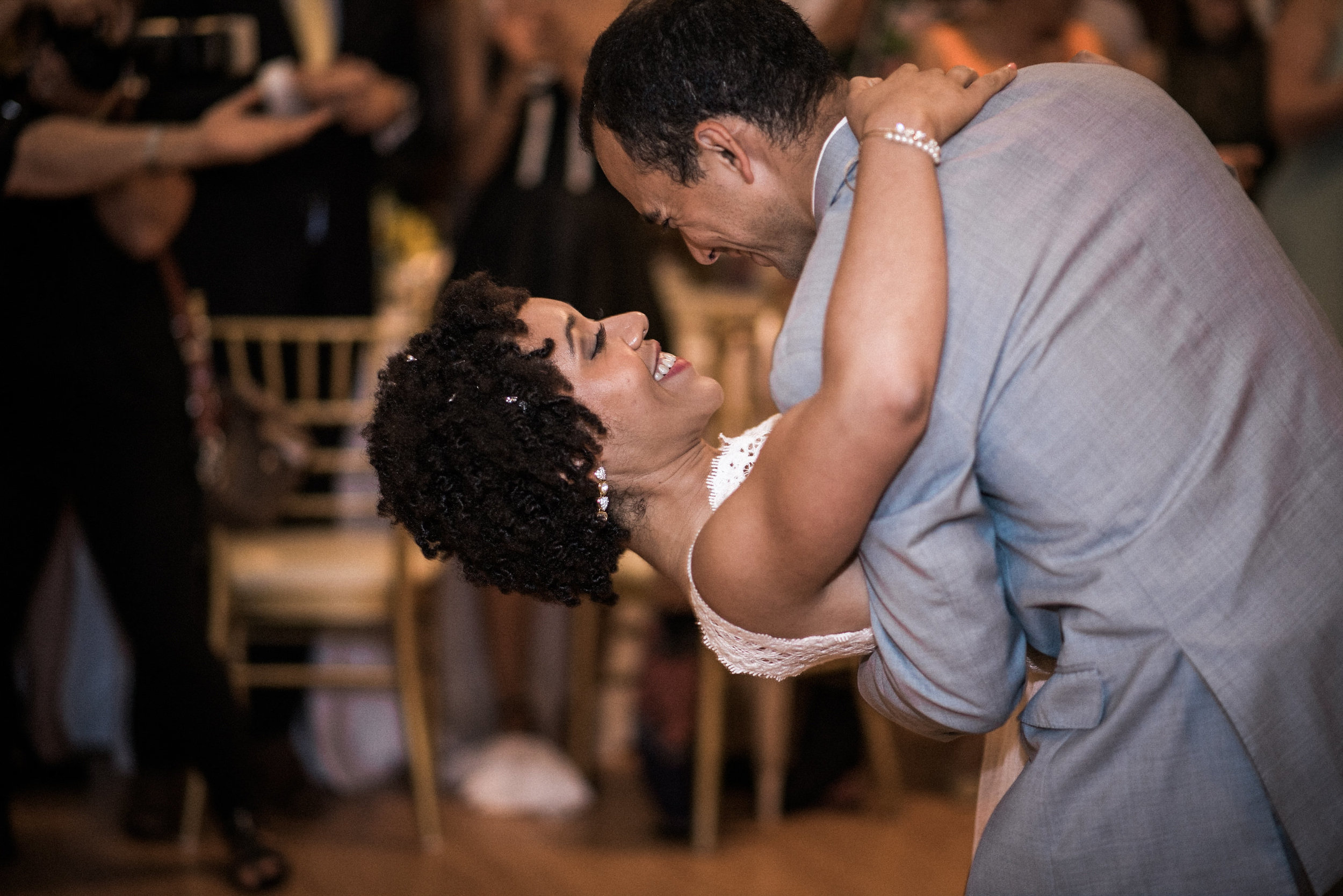 Groom dips bride during dance