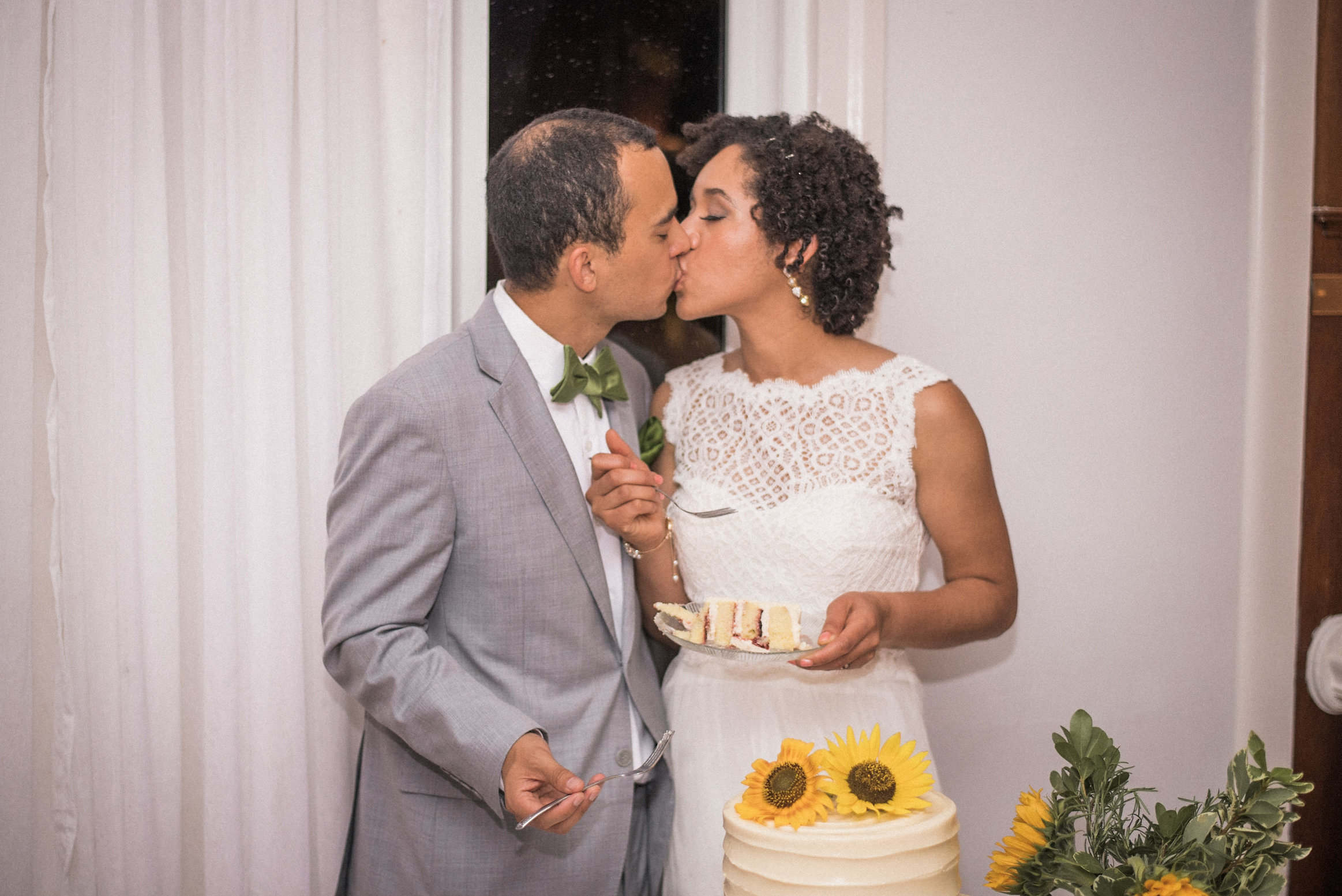 Bride and groom kissing with wedding cake