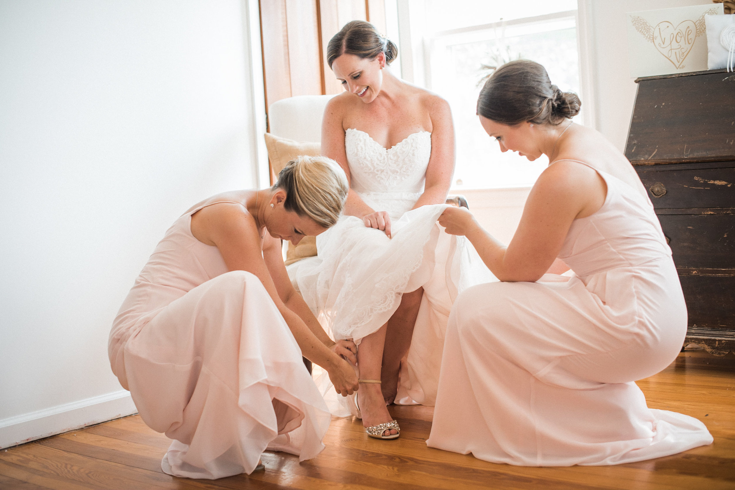 Bridesmaid helping bride put on shoes