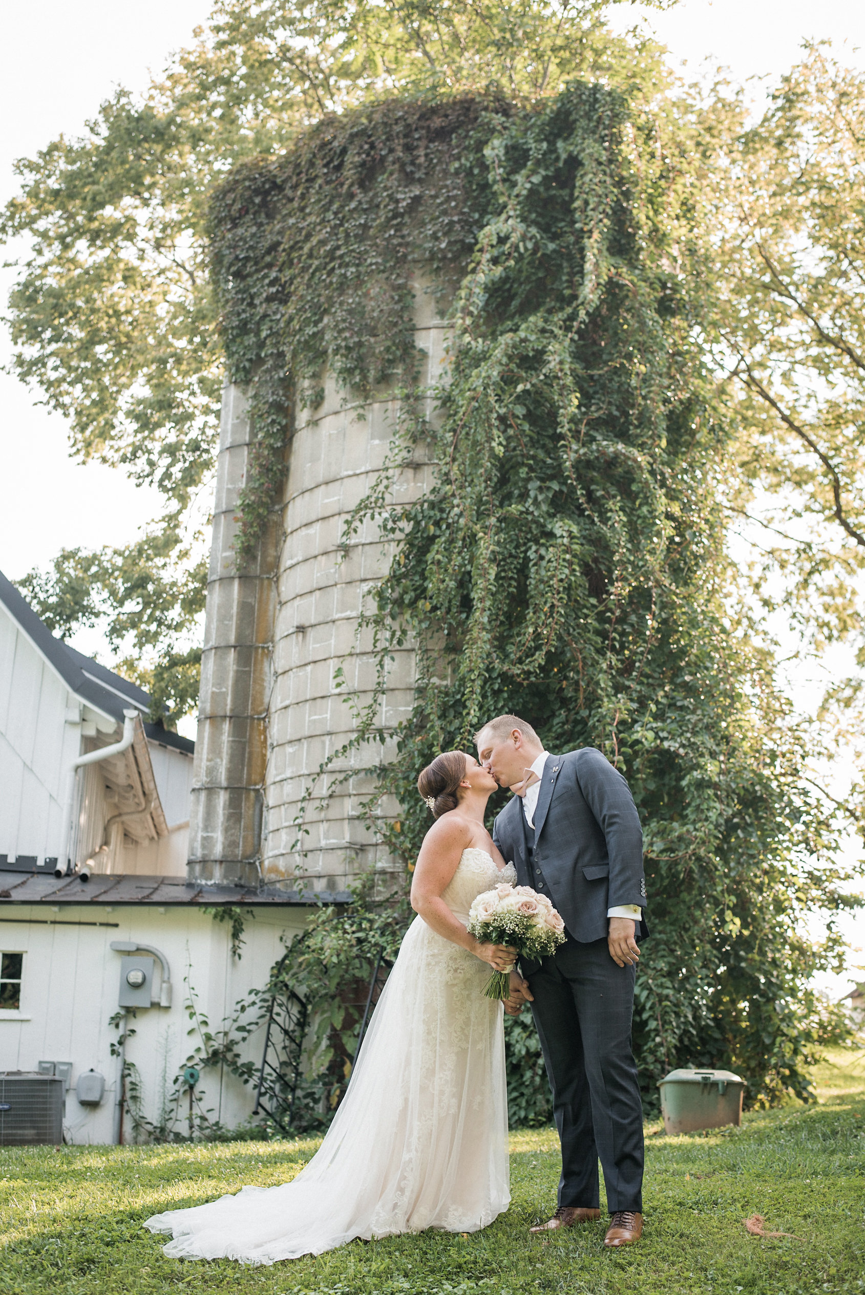 Bride and groom kissing in front of silo