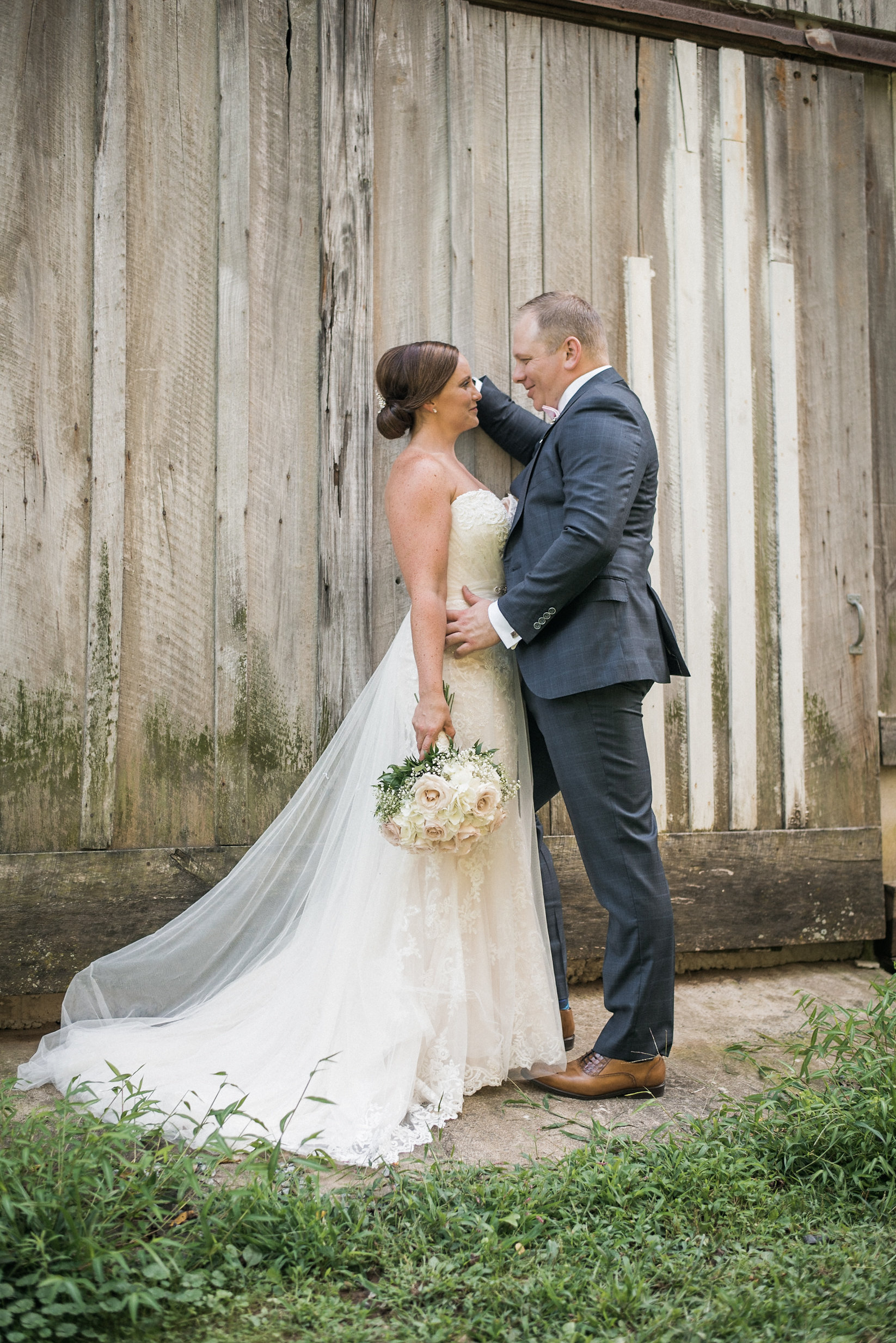 Bride and groom leaning against barn