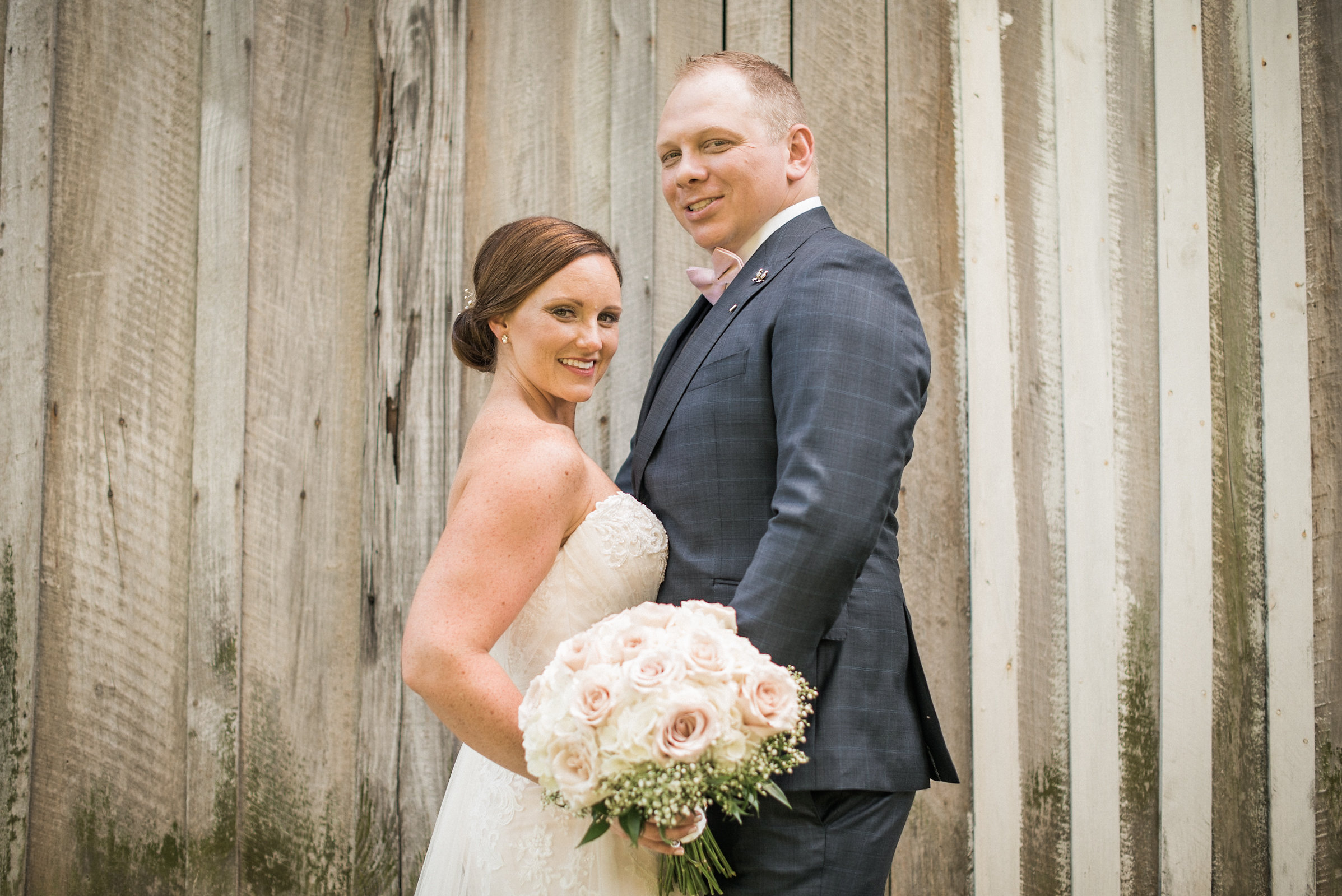 Bride and groom posing in front of barn