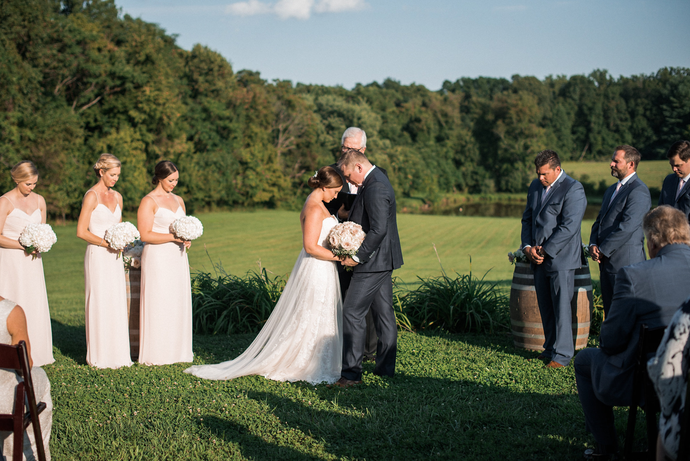 Bride and groom bowing heads during ceremony