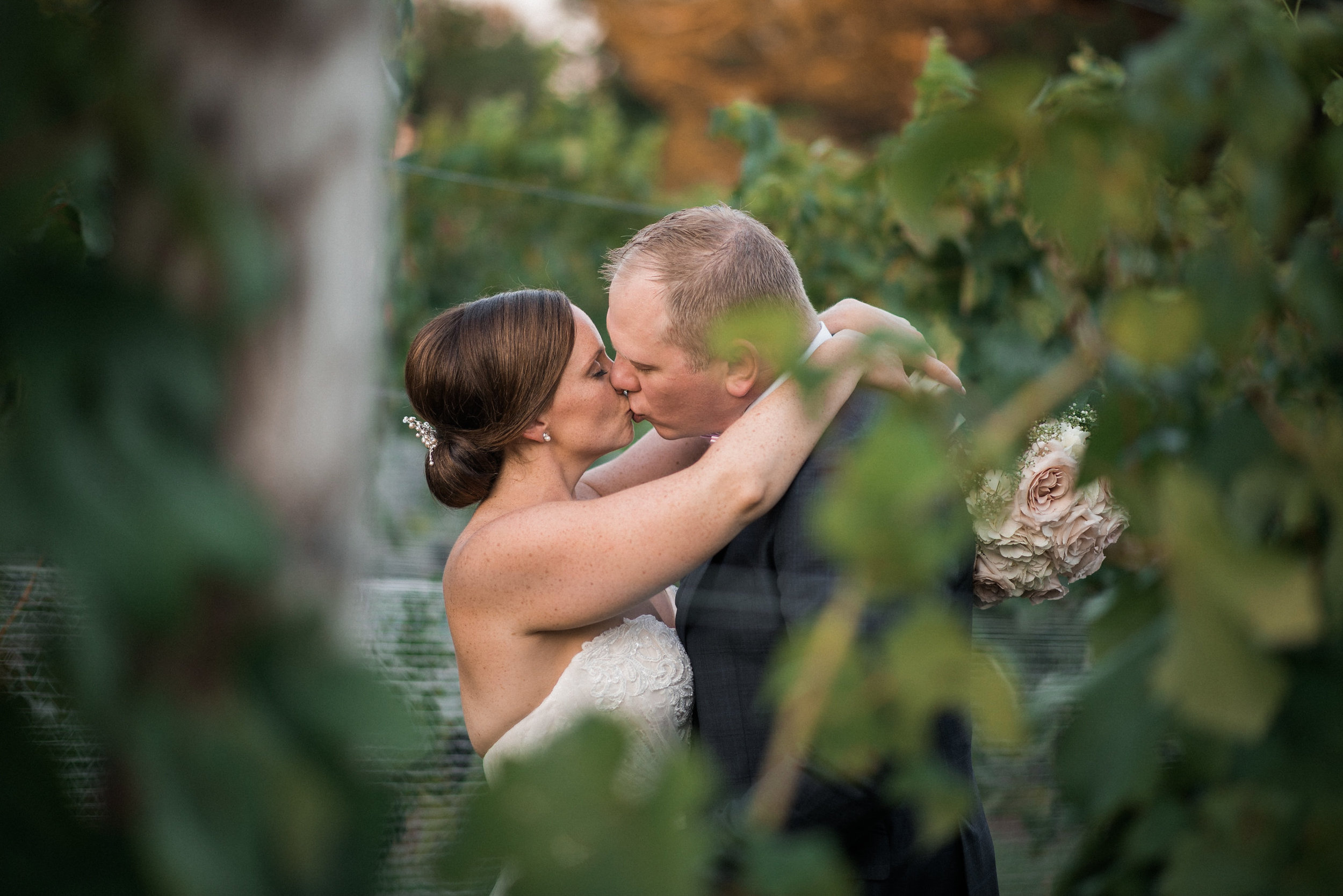 Bride and groom kissing through vines