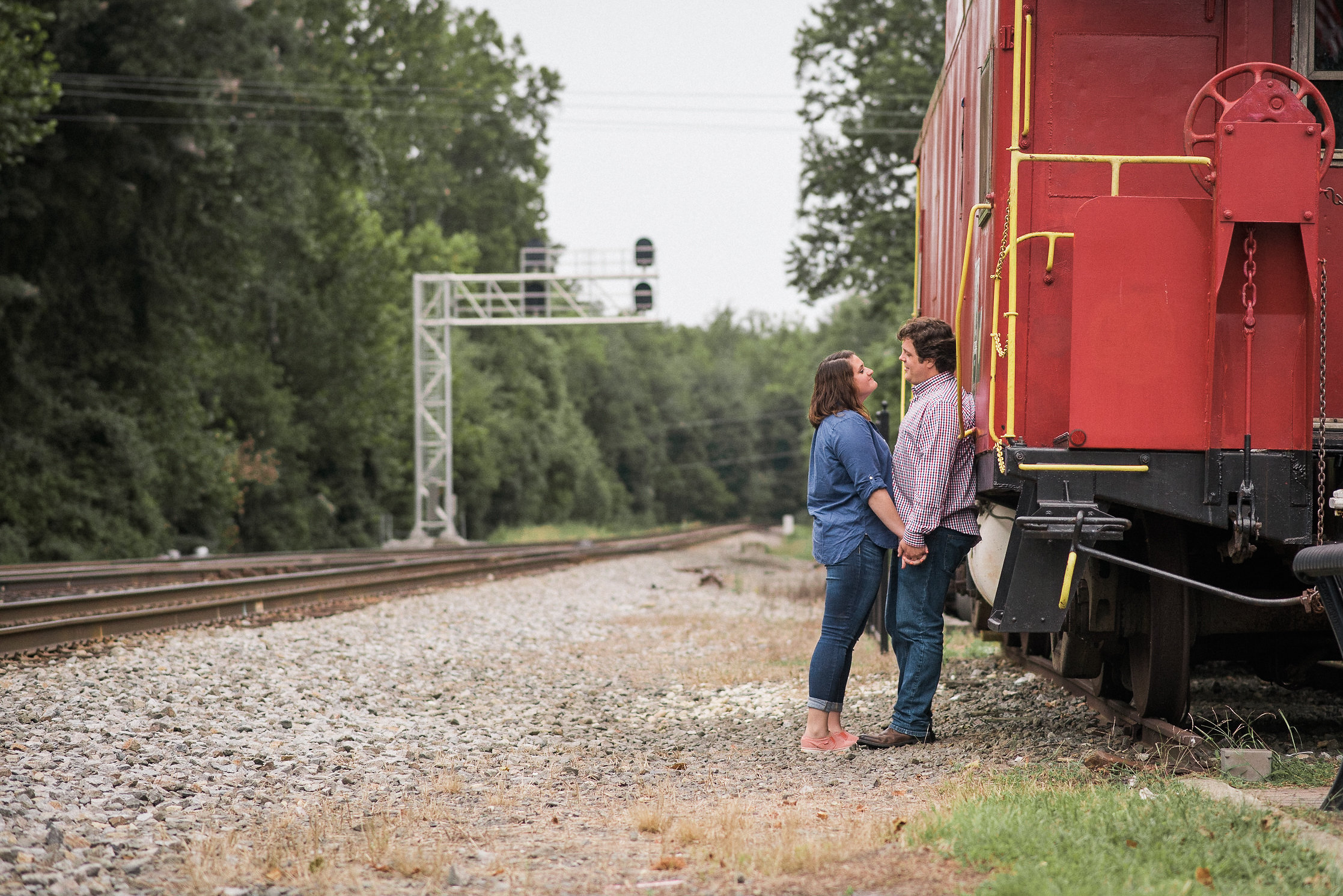 Couple leaning against rail car