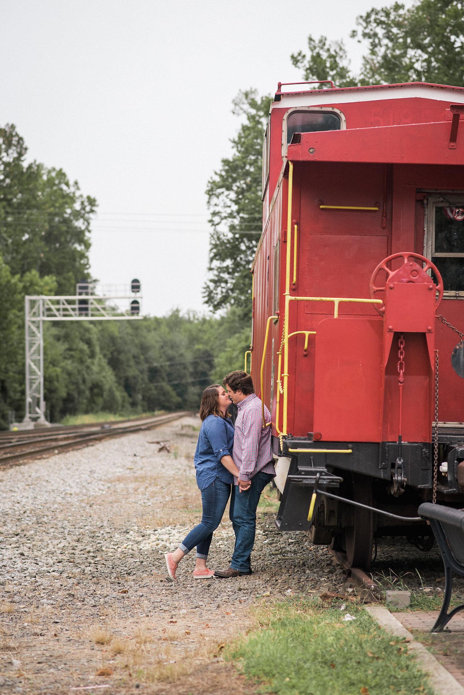 Couple kissing next to rail car