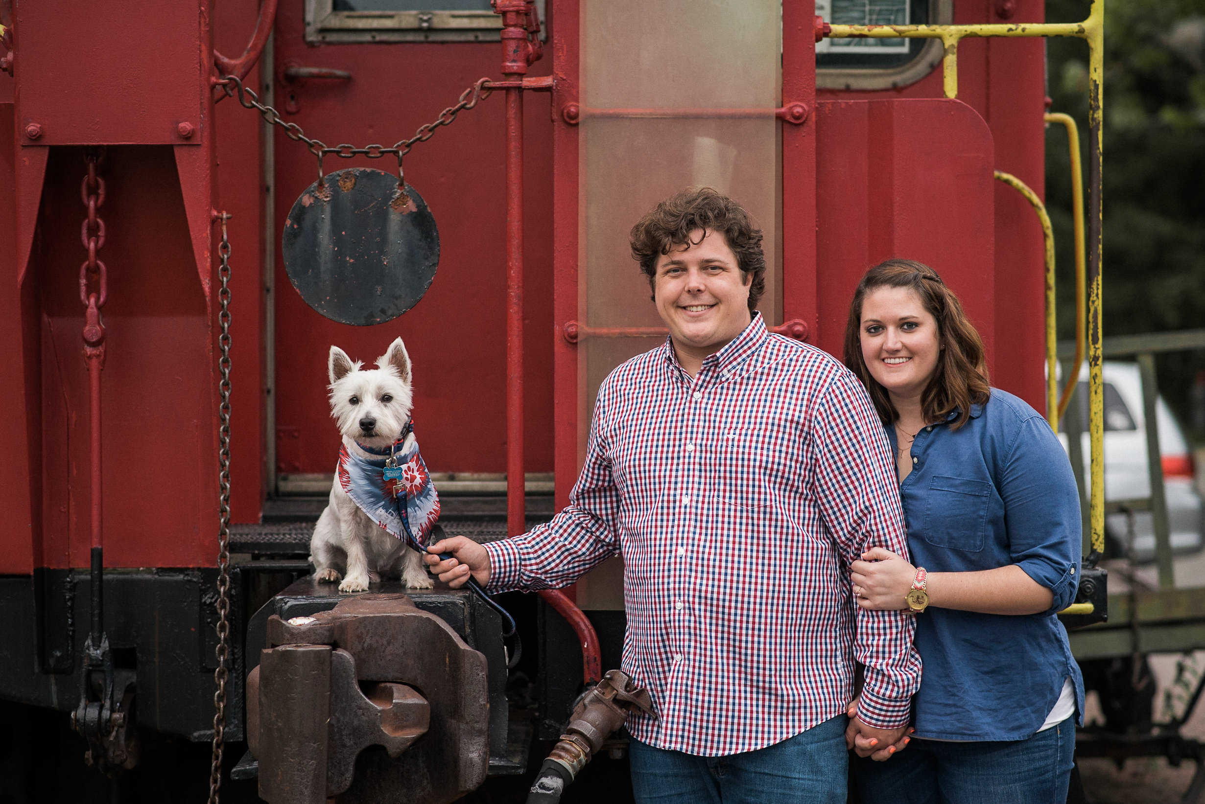 Couple standing by train with dog