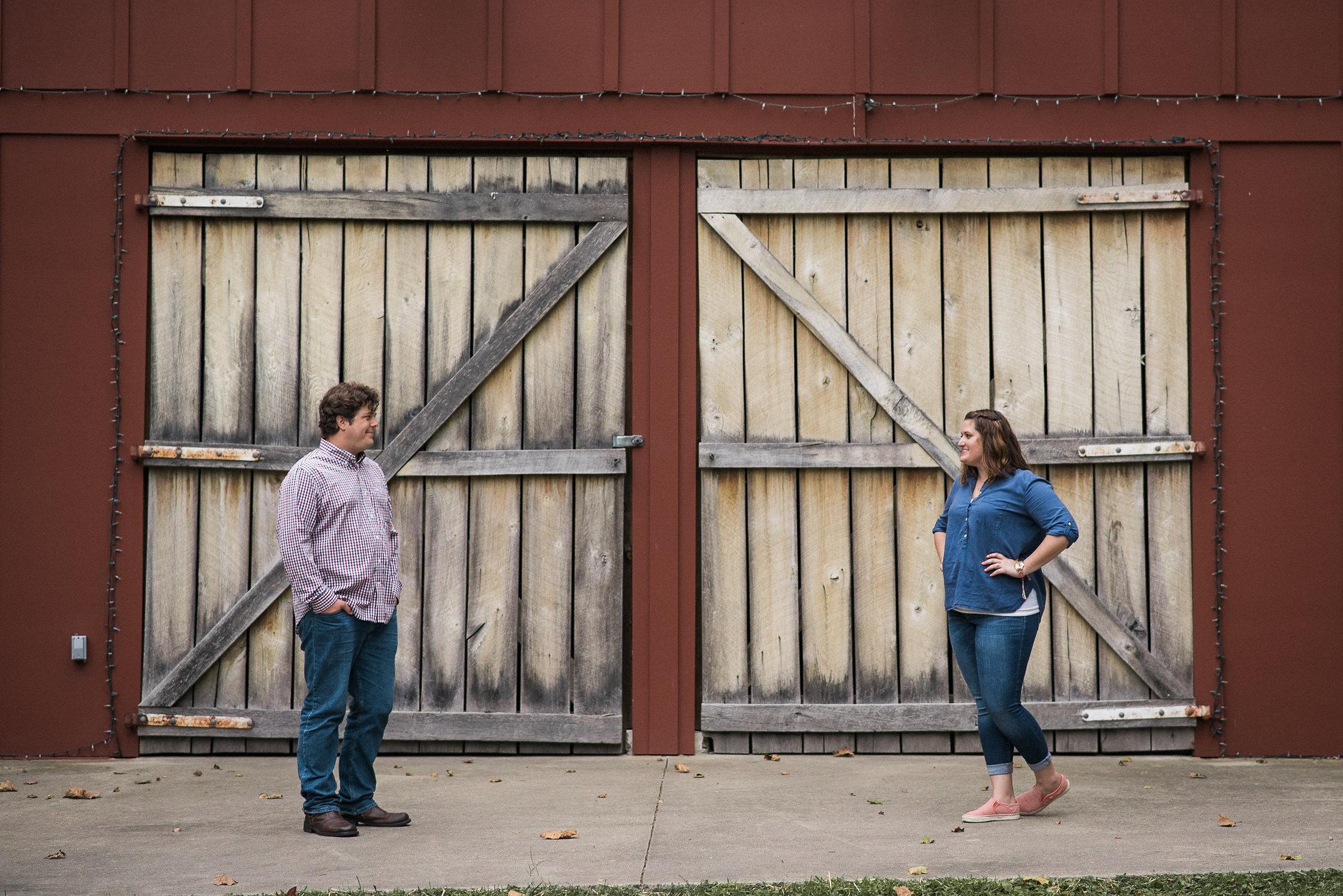 Couple standing in front of barn doors