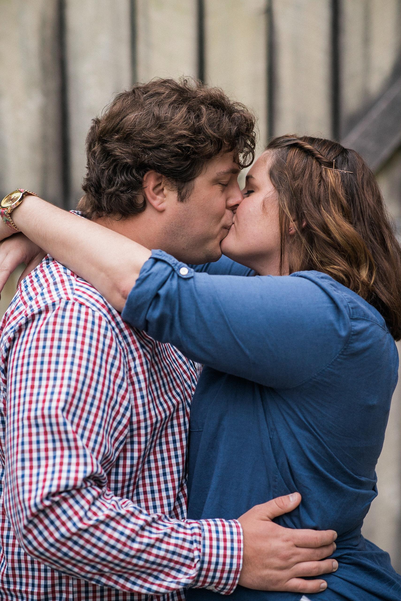 Couple kissing in front of wooden door