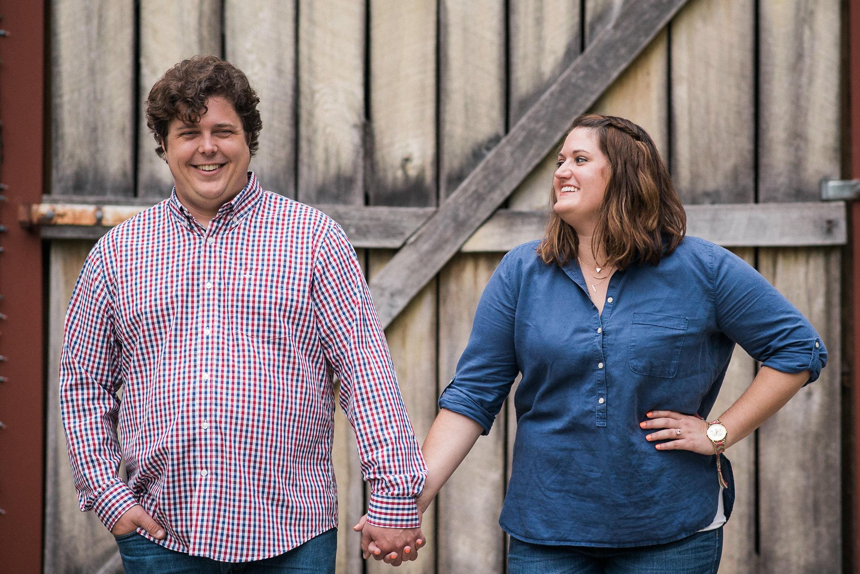 Couple holding hands in front of wooden door