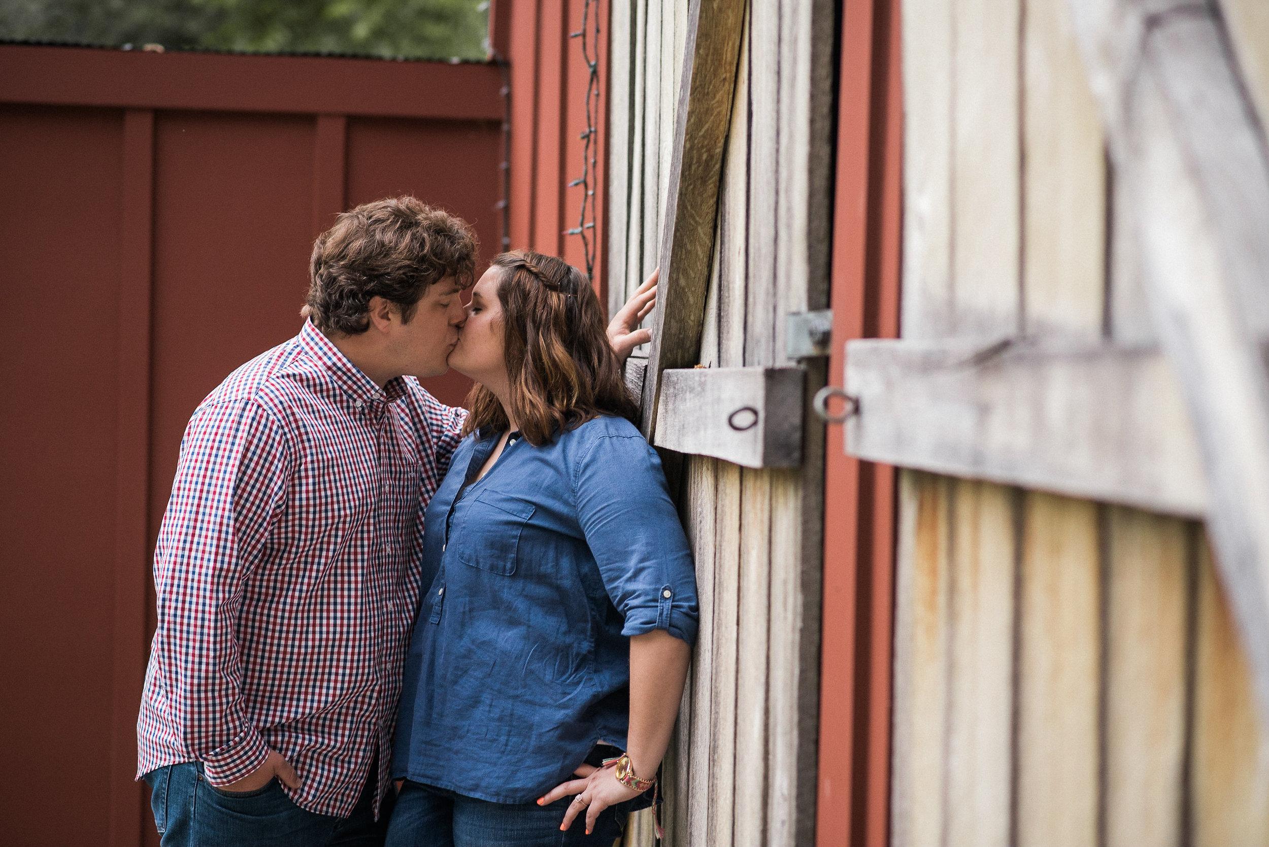Couple kissing against barn door