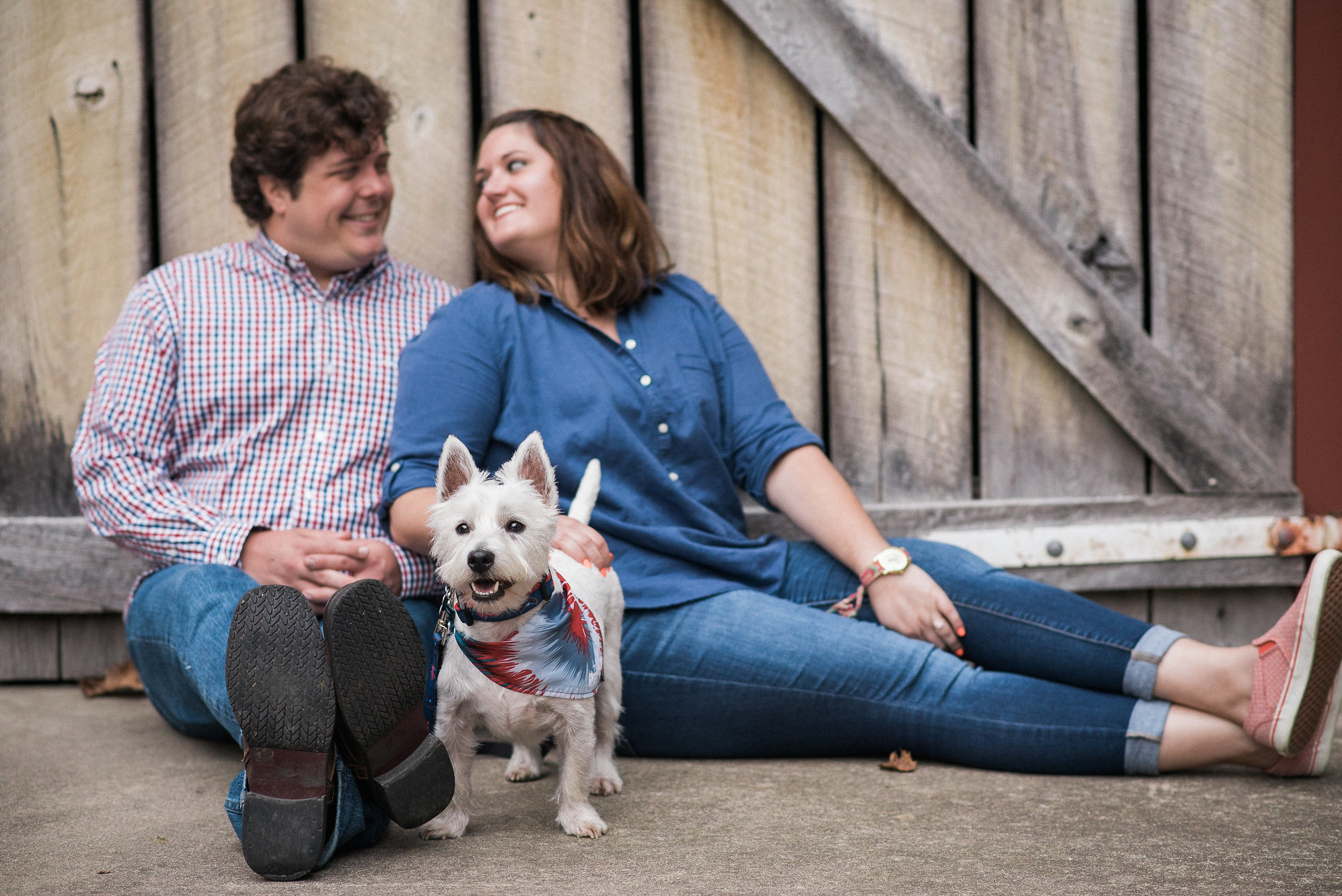 Couple sitting on ground with dog