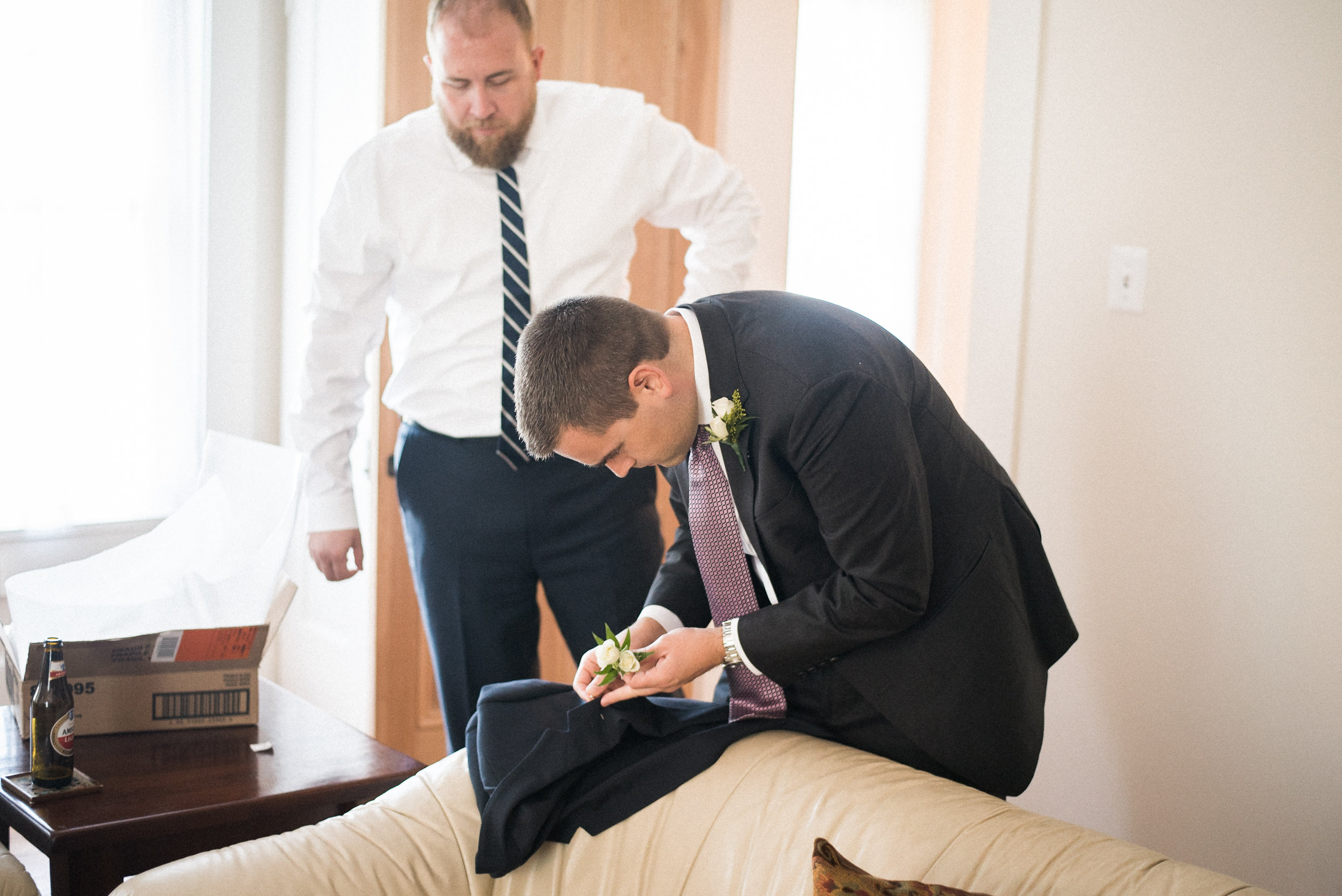 Groom putting flower in jacket