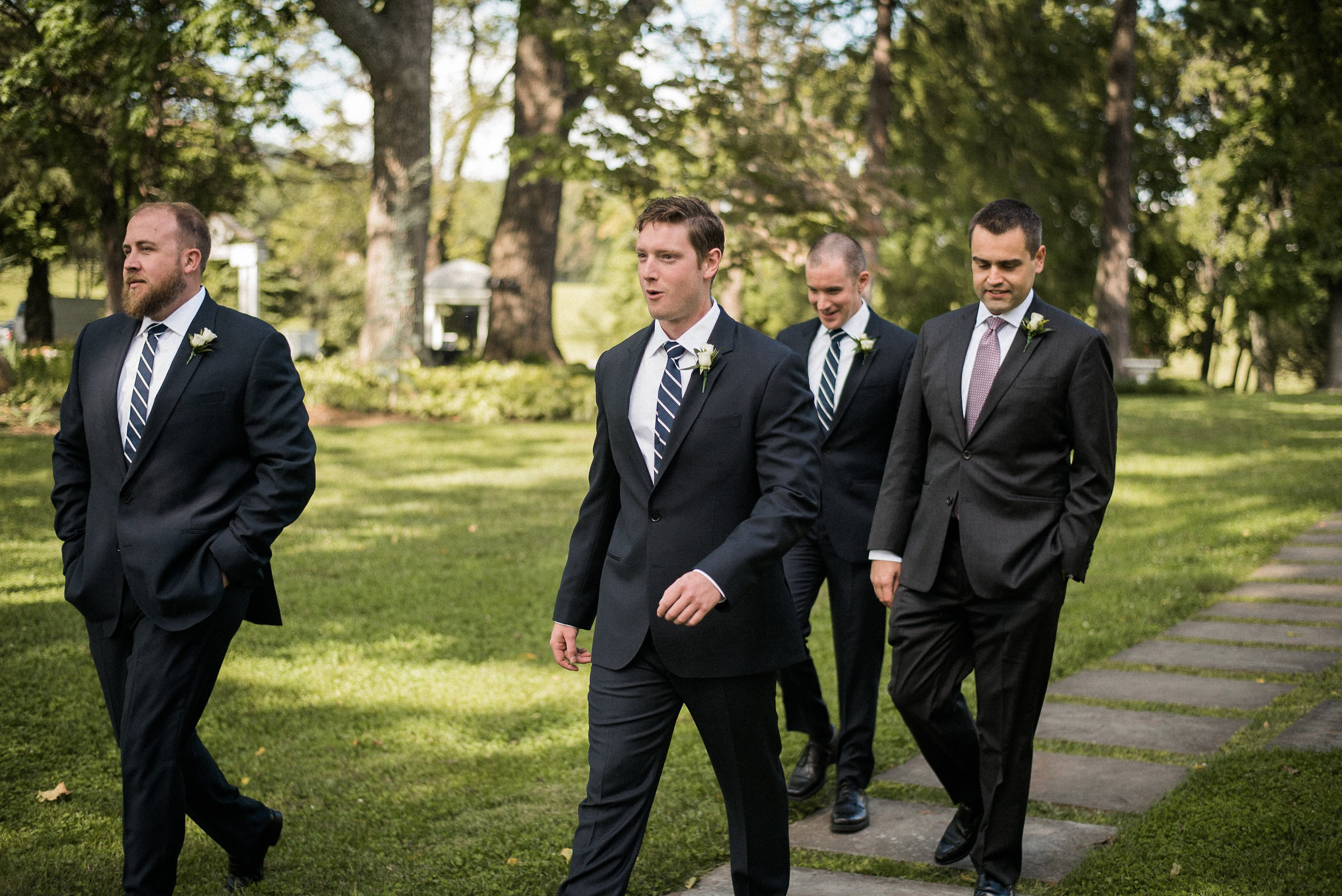 Groom and groomsmen walking across lawn